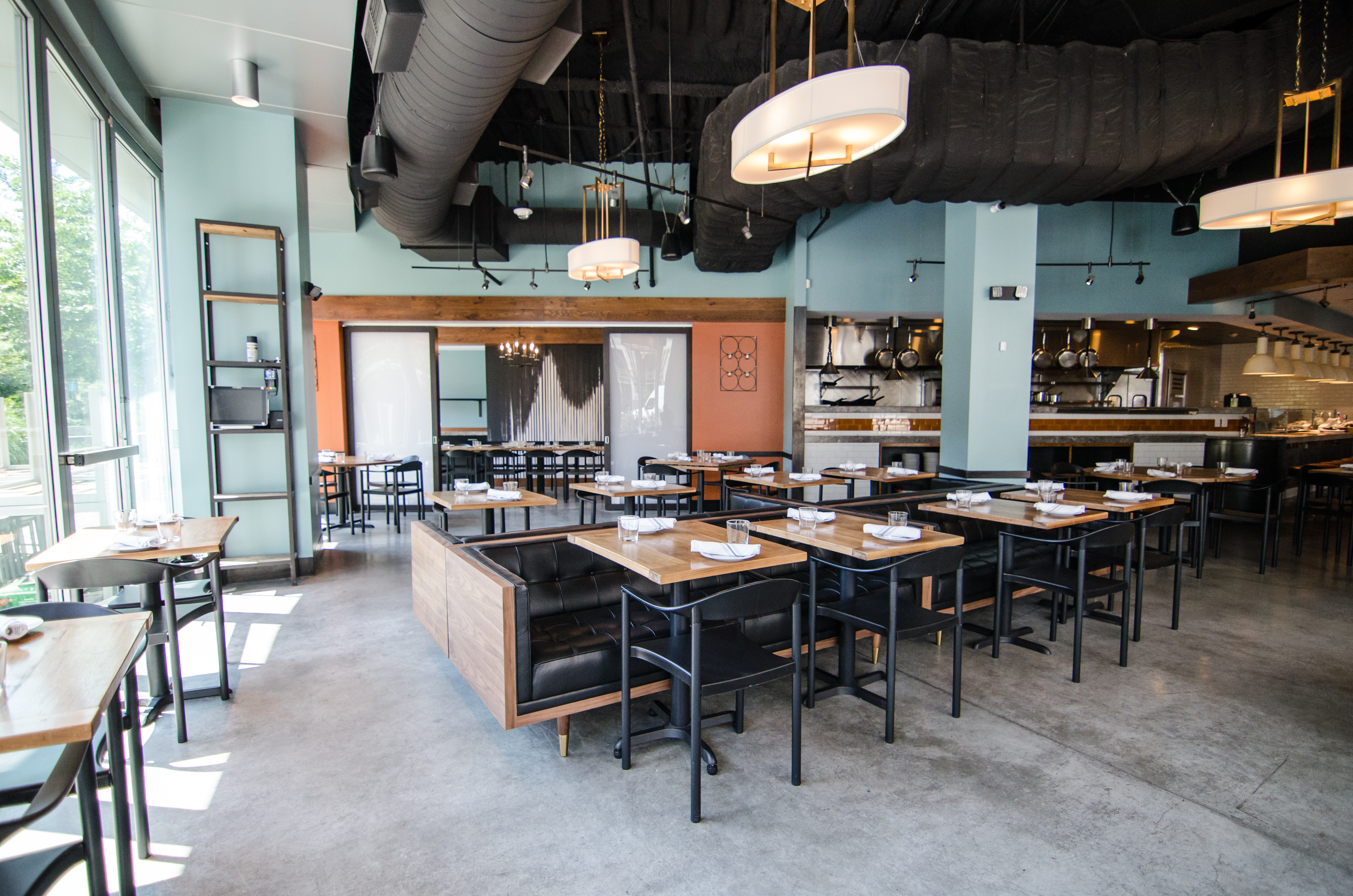 A wide shot of a restaurant space with a polished cement floor, light blue walls, light wooden tables with a mix of black chairs and low black banquette seating, and some orange accents.