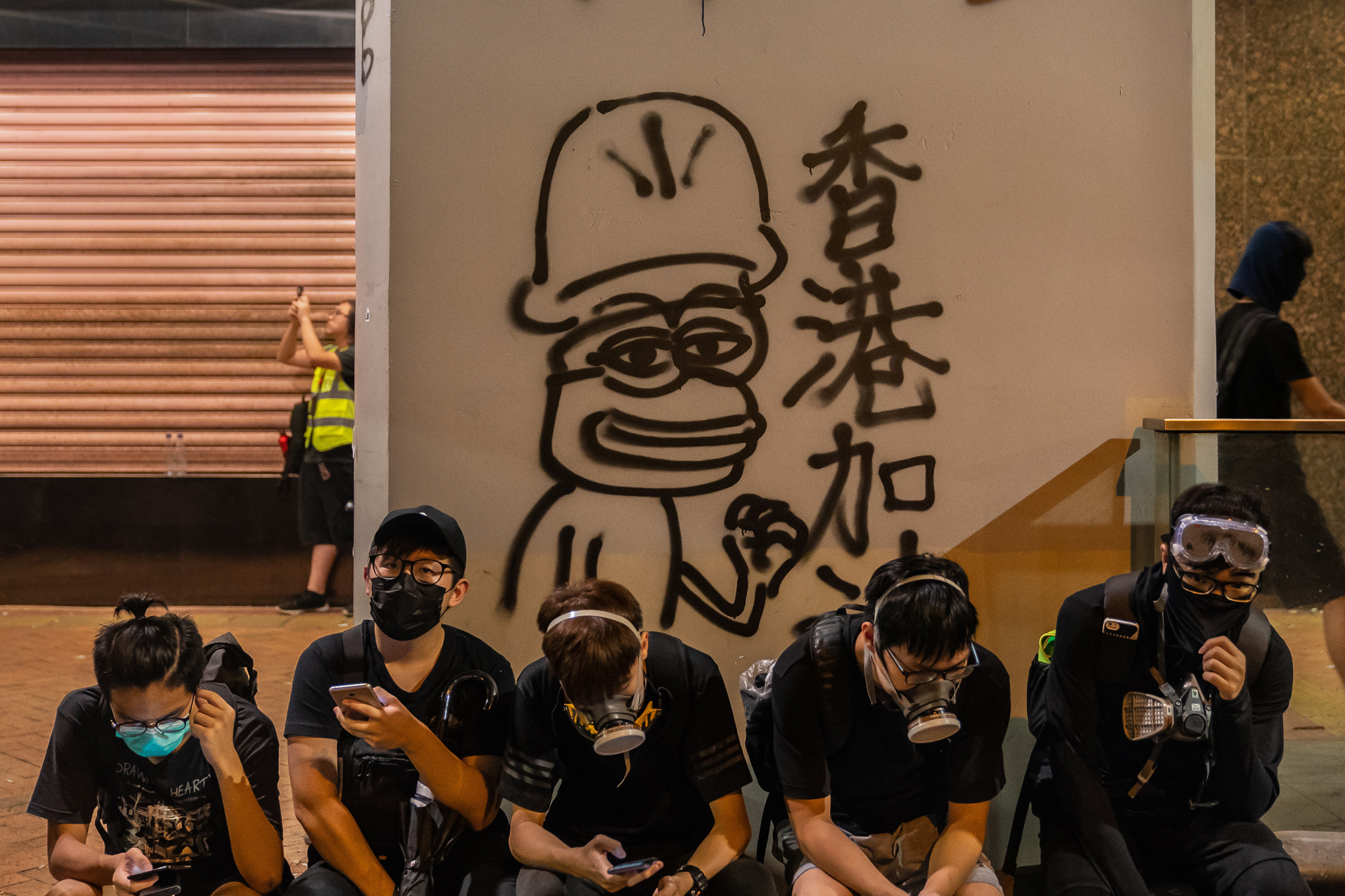 Masked Hong Kong protesters sit in front of graffiti of Pepe the Frog