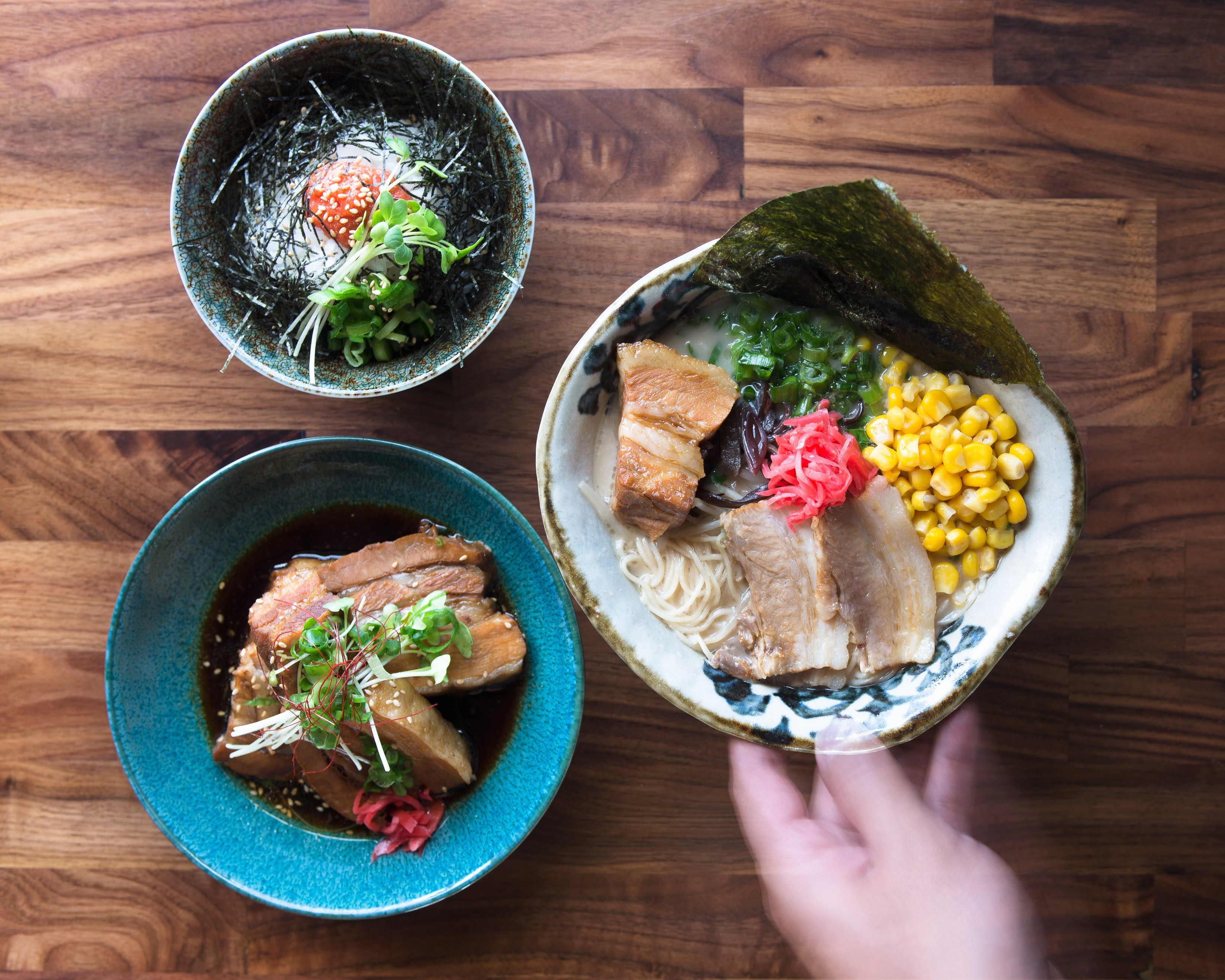 Bowls of ramen garnished with chashu pork, corn, and more from Marufuku Ramen