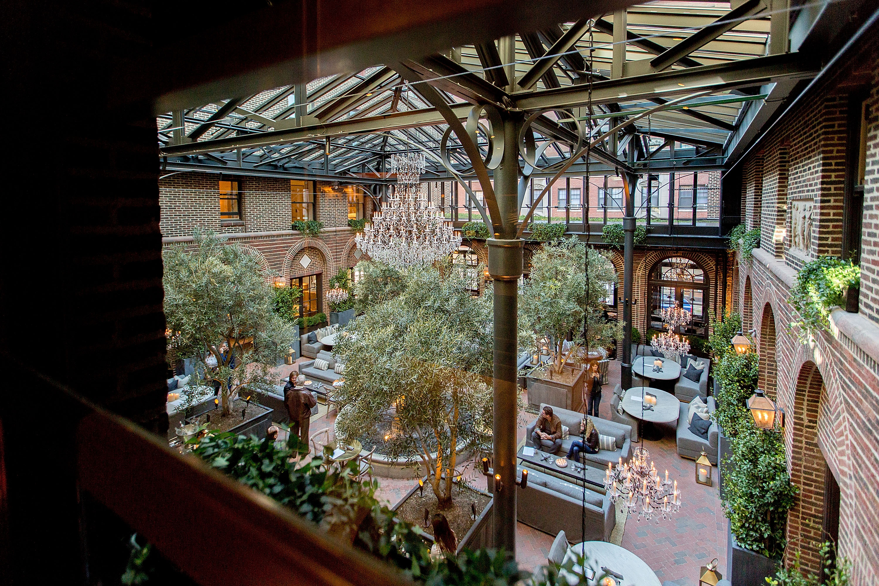 A gorgeous atrium, surrounded in brick walls and topped with a glass roof, filled with chandeliers, gray couches, and trees.