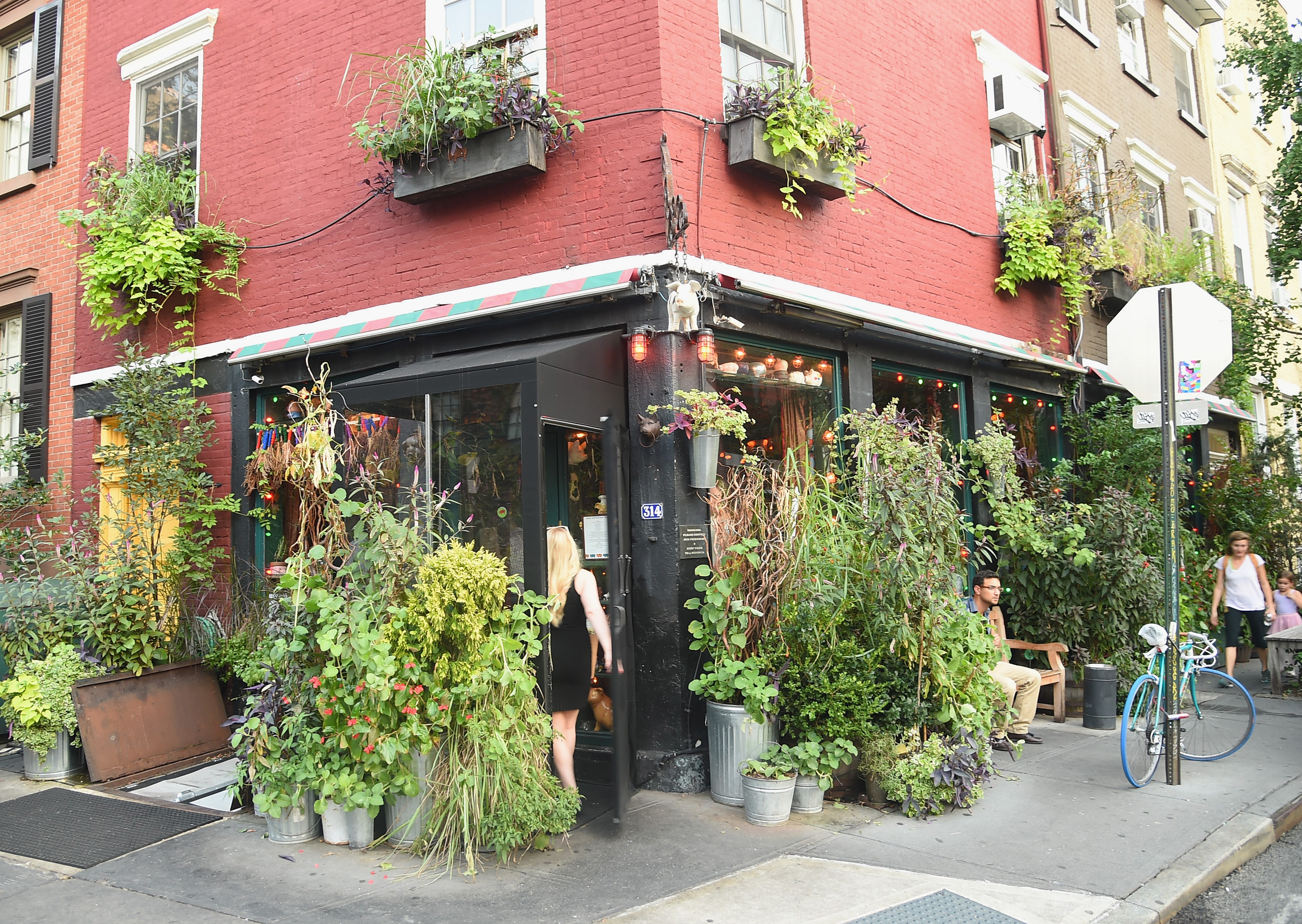 The exterior of the Spotted Pig, which is at a corner and is painted black, with lots of plants