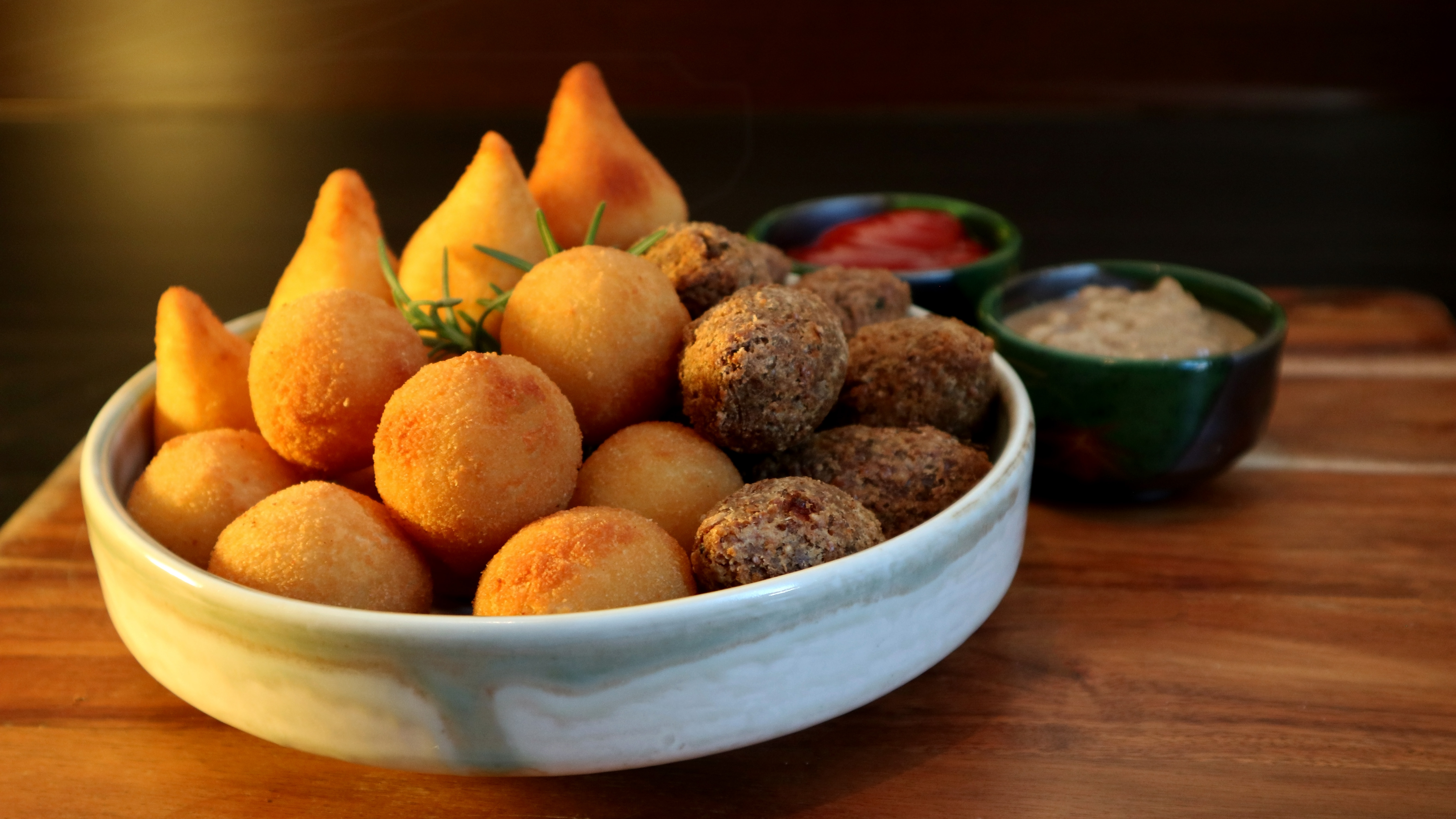 Brazilian snacks of pao de queijo (cheese bread), coxinha (chicken fritters), and quibe (beef fritters)