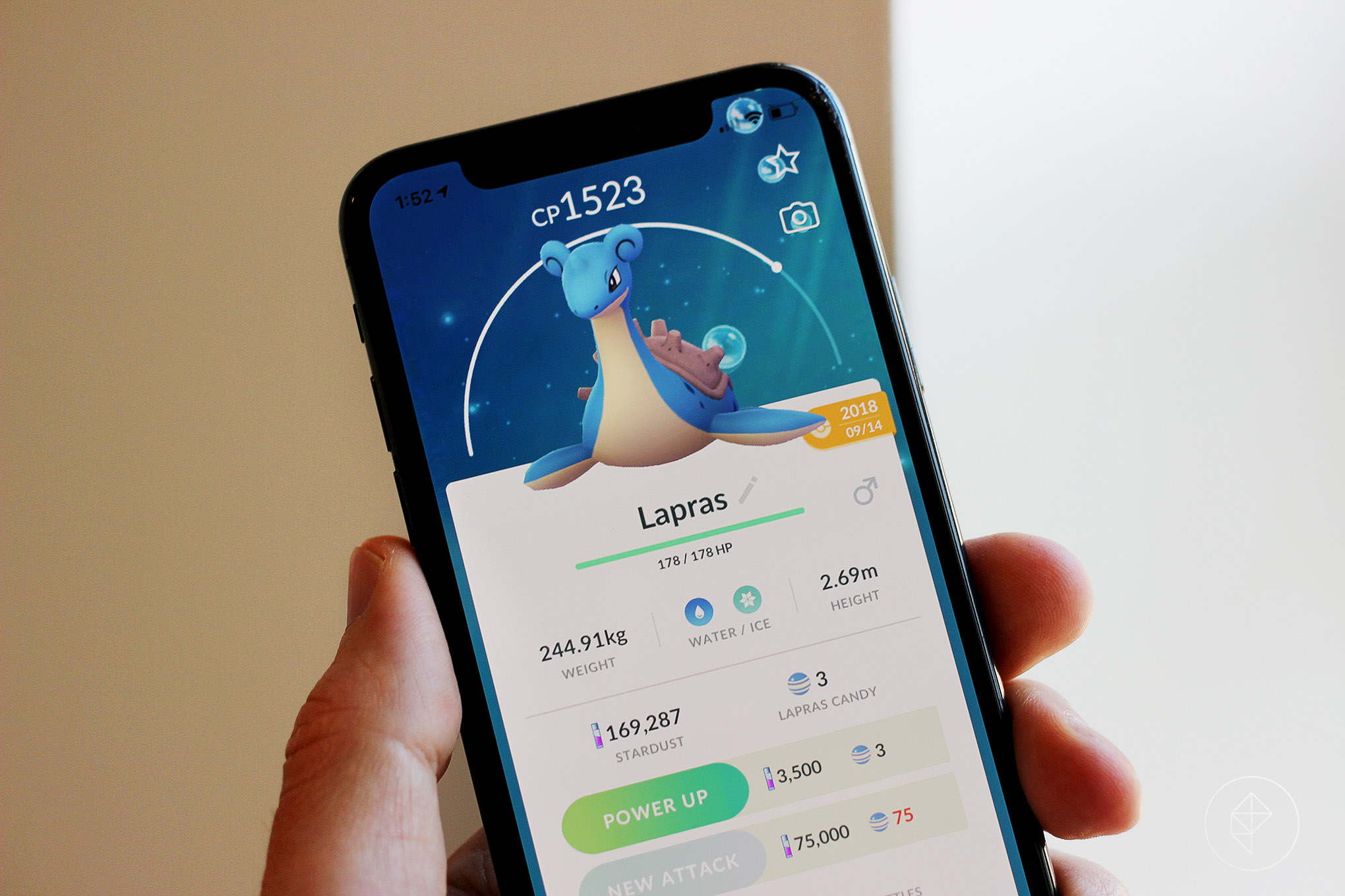 A hand holds up a phone screen with a Lapras stat screen from Pokémon Go