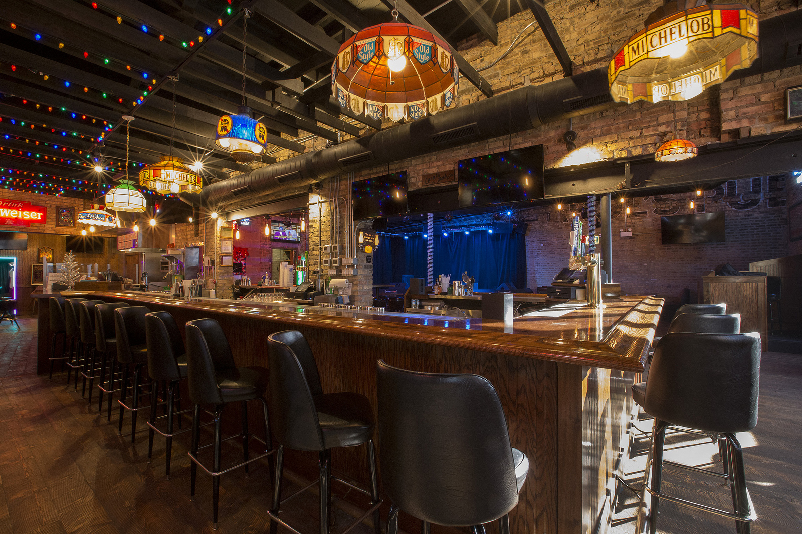 Carol's Pub's interior features hanging lights, black bar stools, a brand new bar, and a musical stage