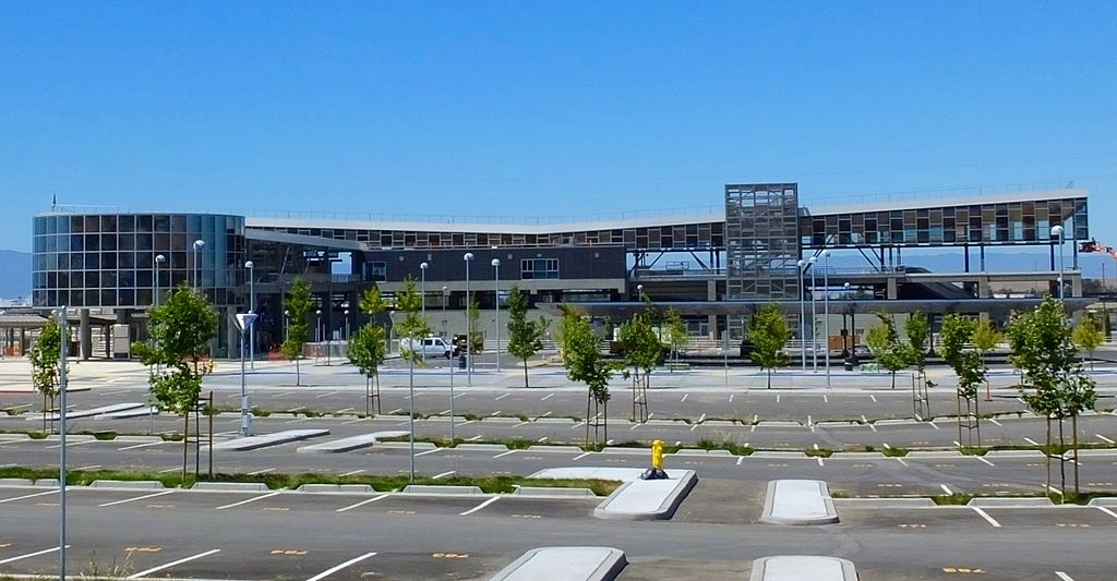 A photo of an elevated train station, taken from a distance, with a parking lot in the foreground.