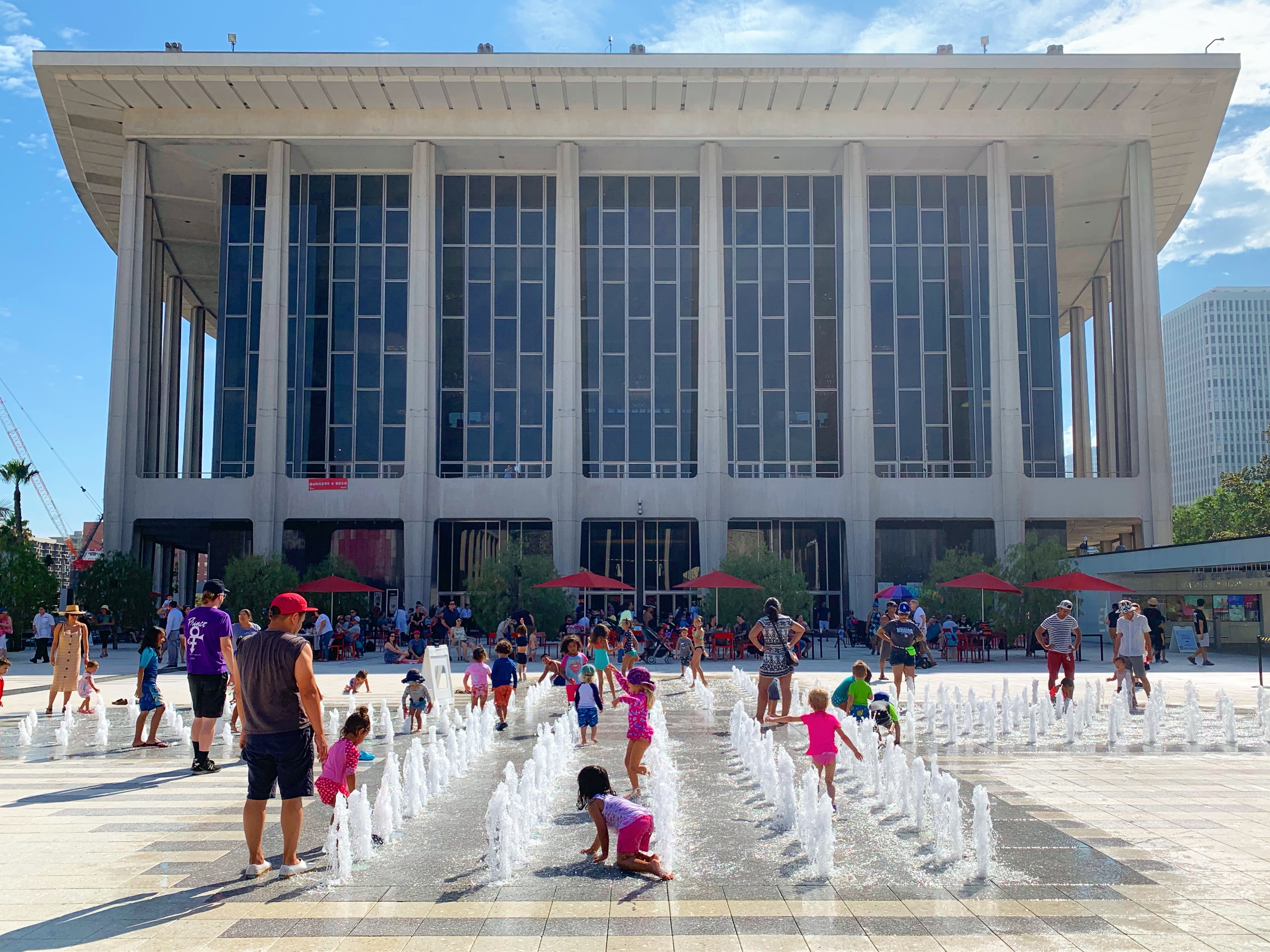 Children in colorful swimsuits play in a splash pad on white plaza in front of a dramatic midcentury performing arts center.