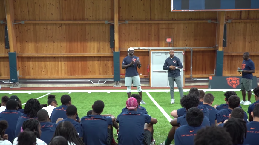 Alex Brown and Matt Forte speak to young football players.