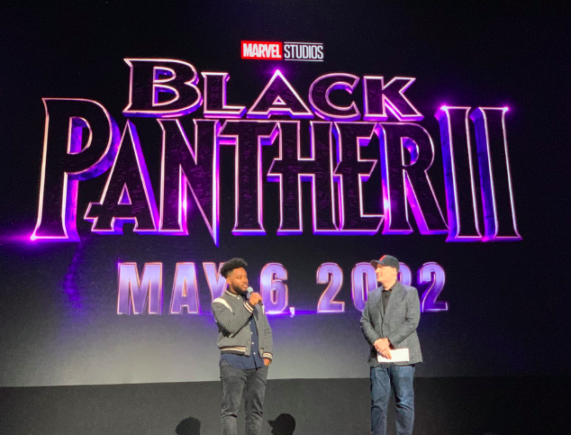 """Two actors stand onstage with handheld microphones in front of a large sign that reads, """"Marvel Studios Black Panther II, May 6, 2022."""""""