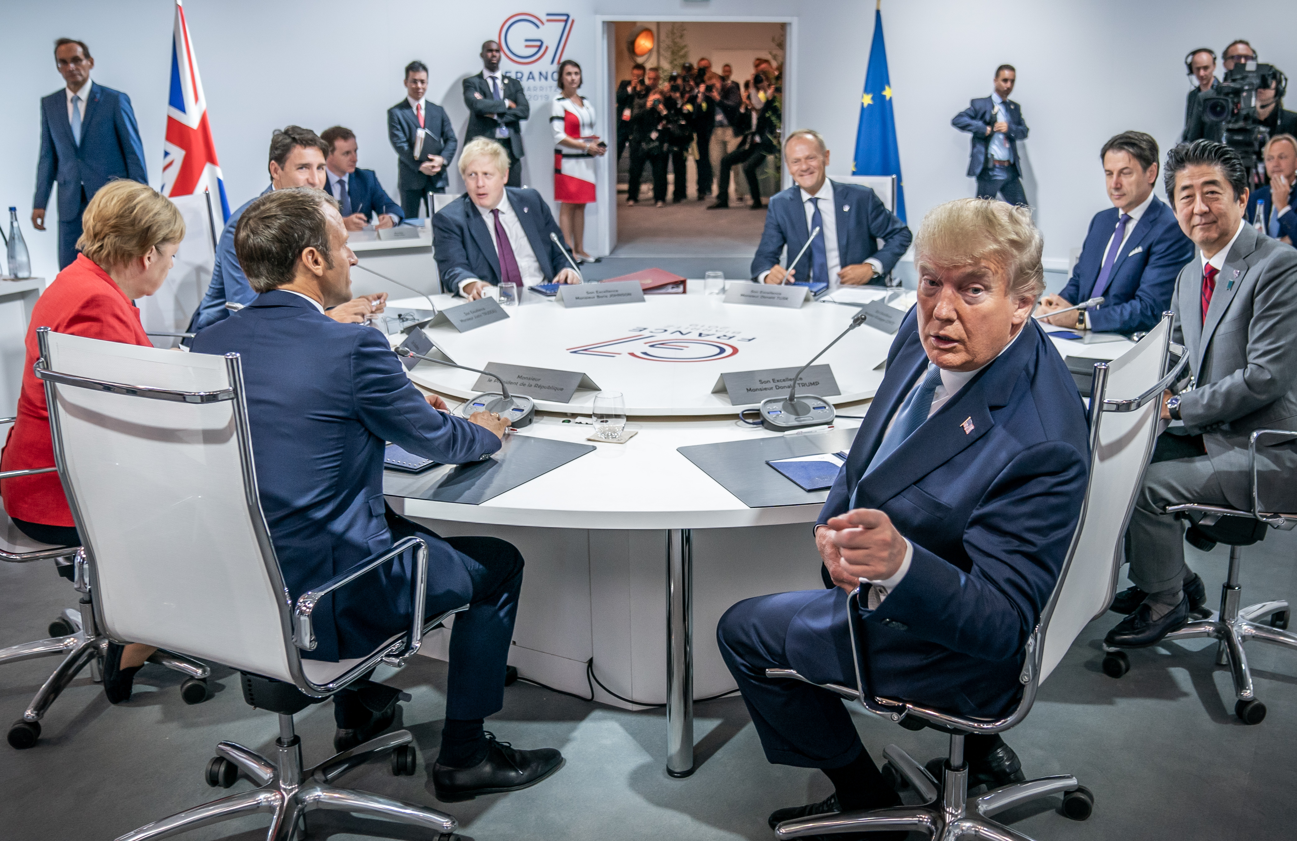 Donald Trump points at the viewer as other G7 leaders speak to one another at a round table with the summit's red, white, and blue logo.