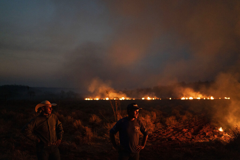 Neri dos Santos Silva, center, watches an encroaching fire threat in Brazil