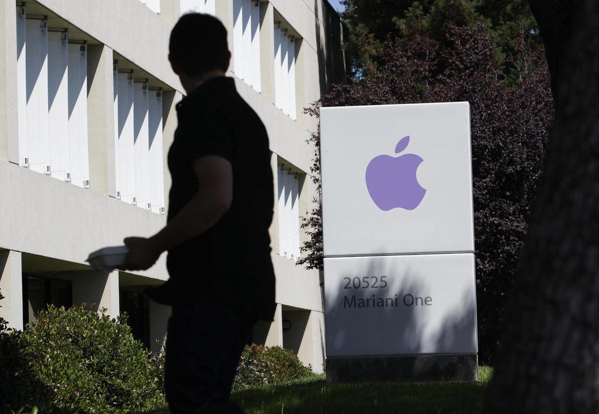 An Apple employee walks between Apple buildings at Apple headquarters in Cupertino, Calif., Thursday, Aug. 25, 2011.