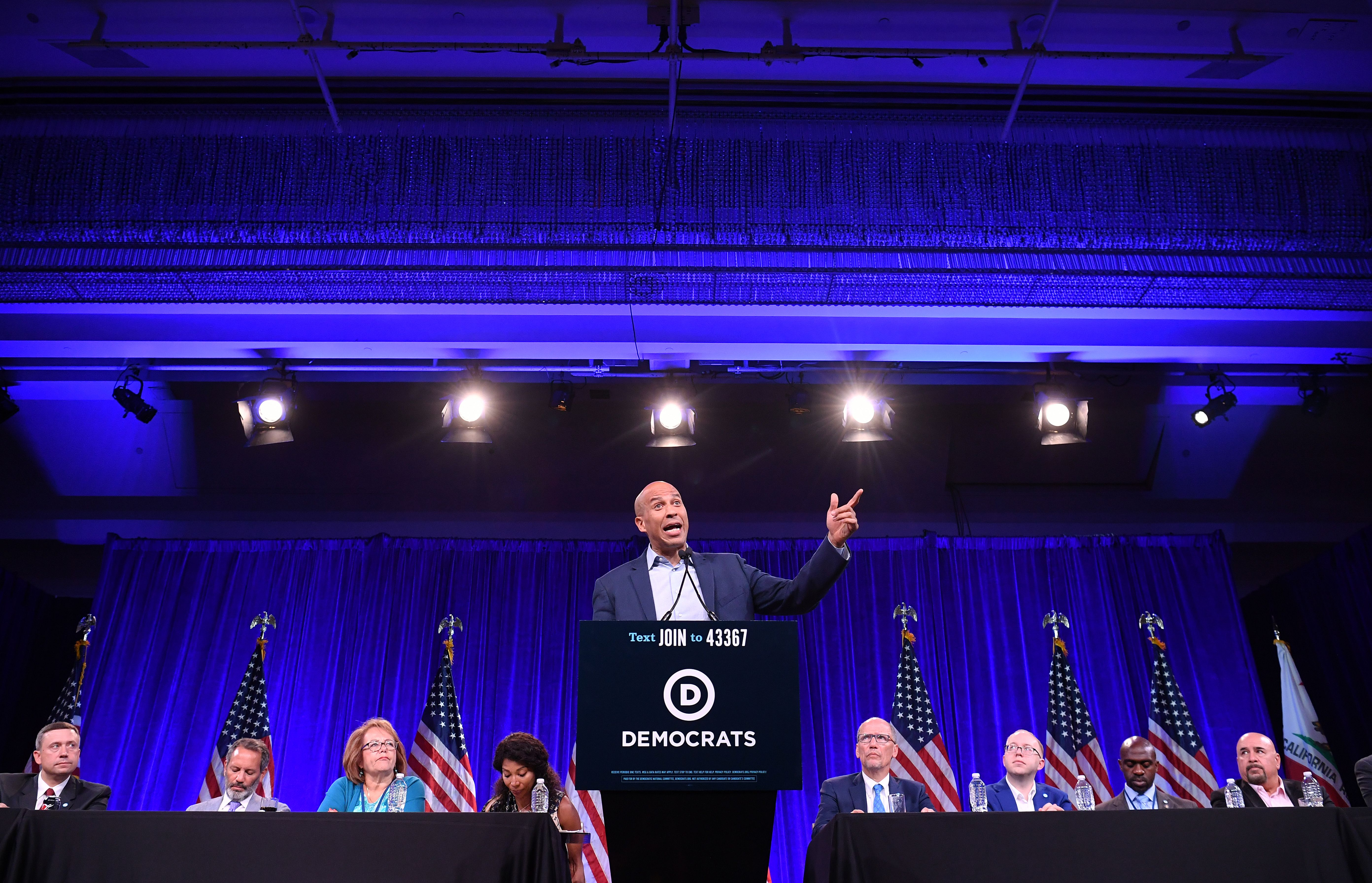 Booker stands at a podium with the Democratic Party logo, in front of party leaders and a row of American flags.