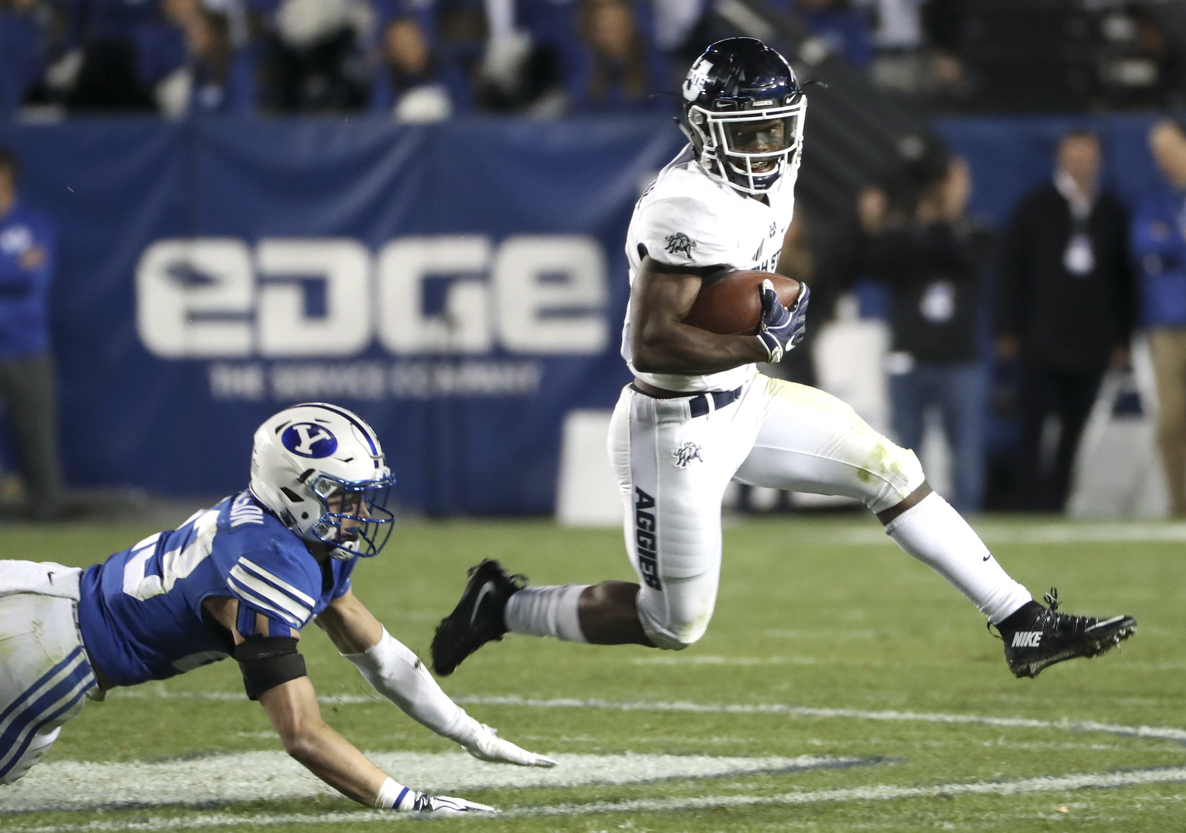 Utah State Aggies running back Darwin Thompson (5) sweeps around the end during the Utah State versus BYU football game at LaVell Edwards Stadium in Provo on Friday, Oct. 5, 2018.