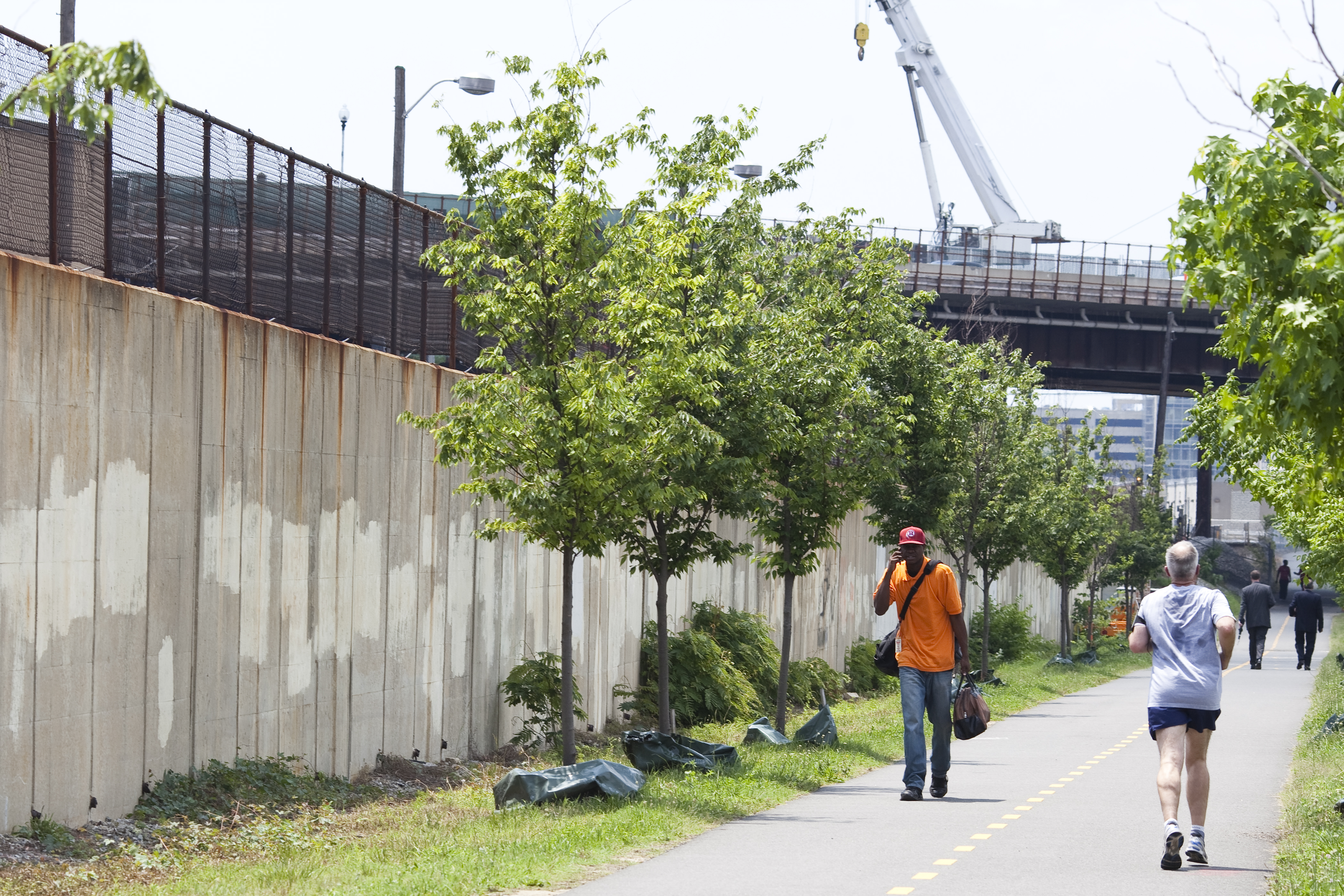 Pedestrians along a multiuse trail surrounded by trees and elevated train tracks.