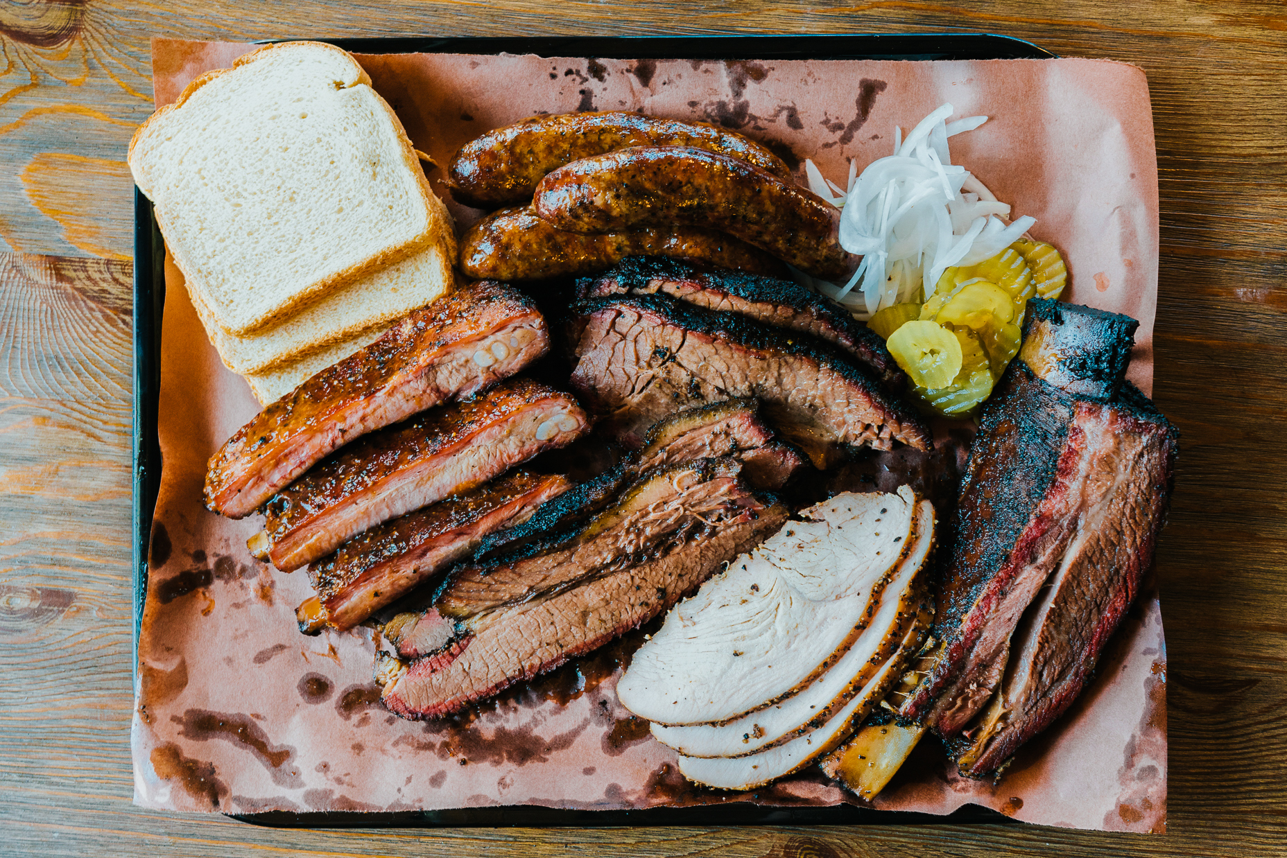 A tray of brisket, sausages, turkey, and bread and pickles