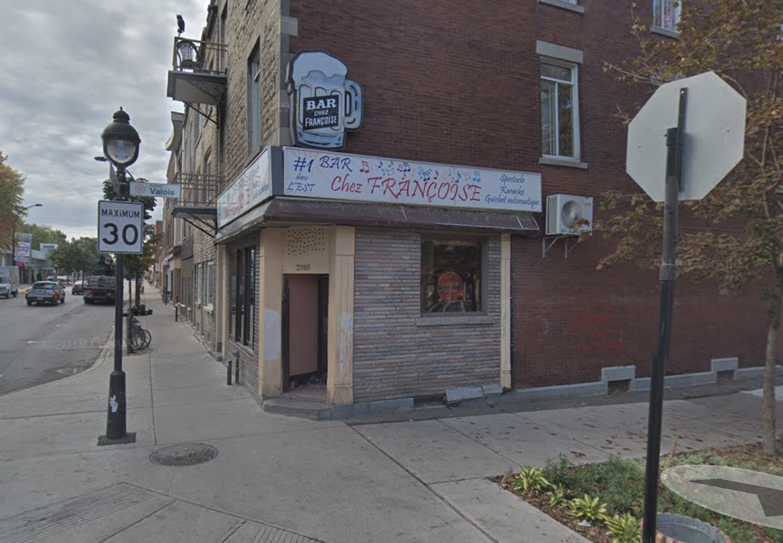 An external view of Bar Chez Francoise including the sidewalk and its door on the corner of Sainte-Catherine and Valois streets.