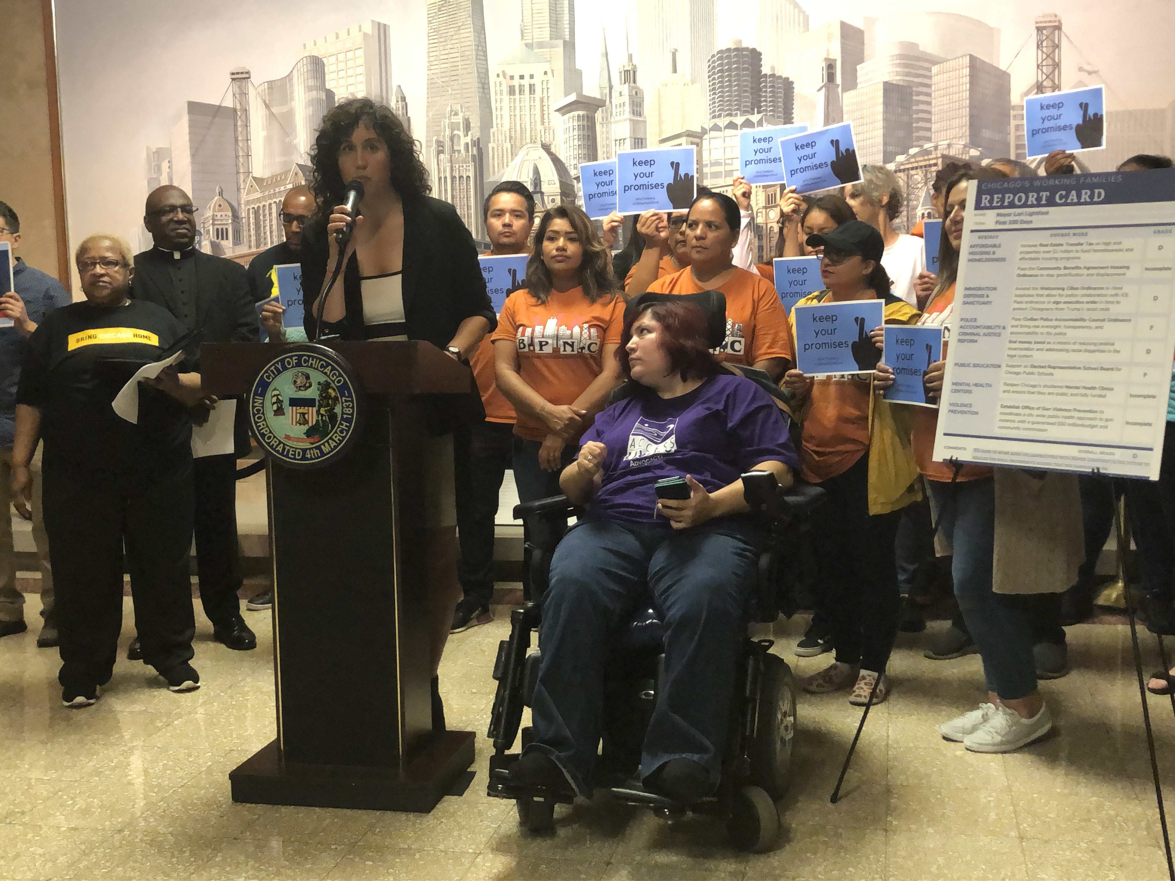 Emma Tai (left) and Michelle Garcia, from Access Living, stand with other community activists at City Hall to issue their report card for Mayor Lori Lightfoot's first 100 days in office.