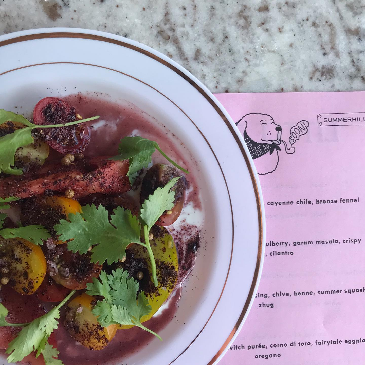 A bowl of tomatoes and broth with a pink Little Bear menu beside it