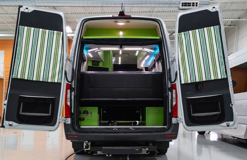 The rear of a Mercedes camper van features open doors with striped green window coverings, a bed shelf, and green storage boxes underneath.