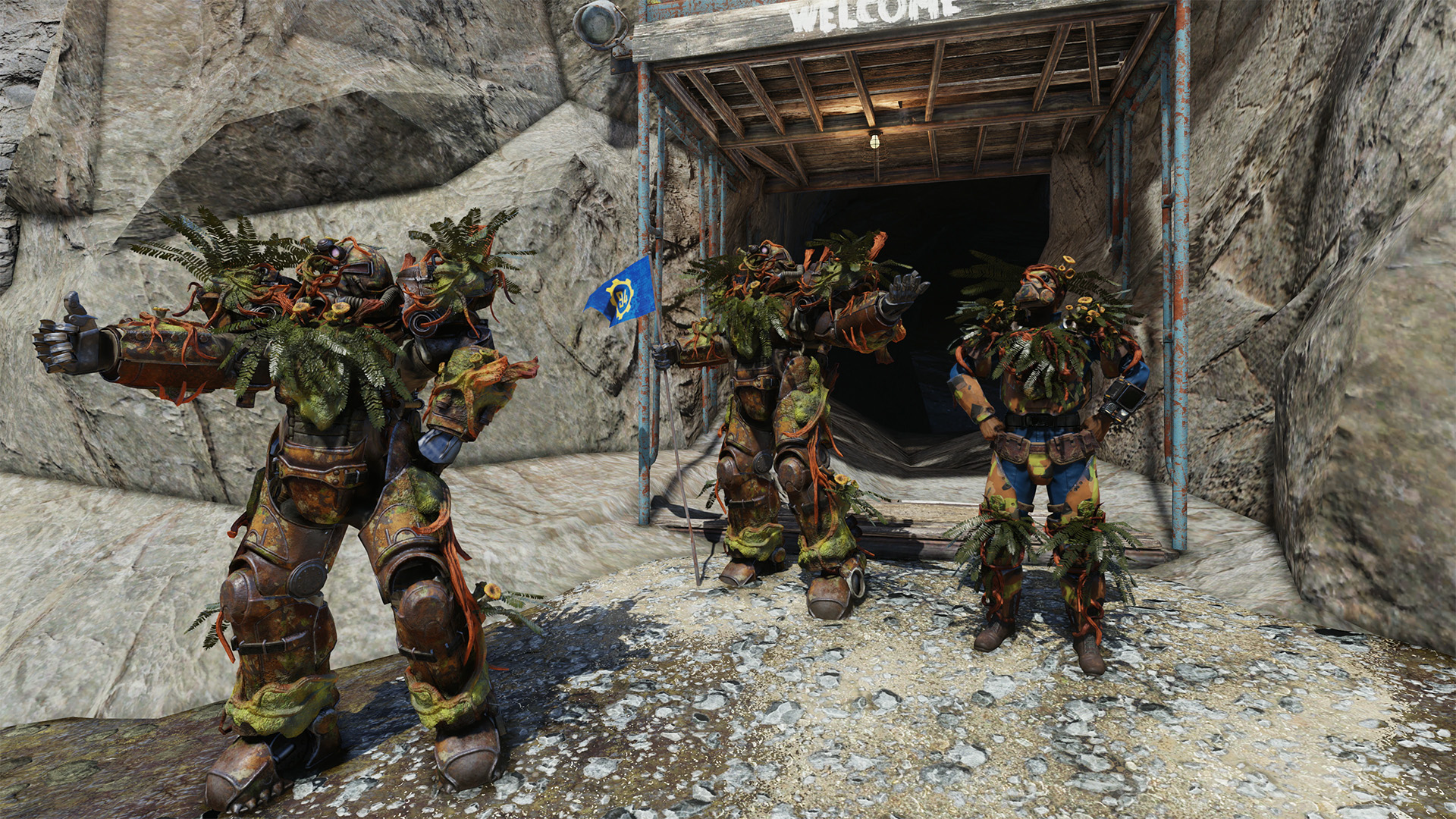 Fallout 76 - three players, wearing end game Vault gear, pose outside Vault 94 and give the thumbs up.