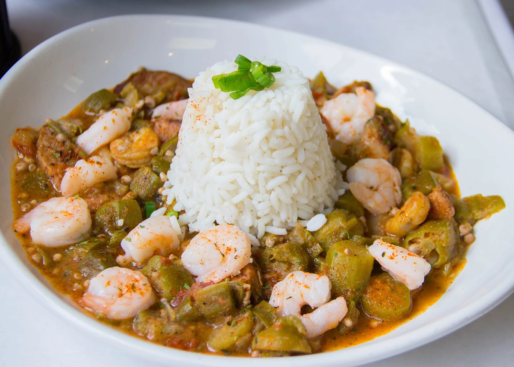 A dish with an okra, tomato, and sausage base topped with shrimp and served with white rice in the center