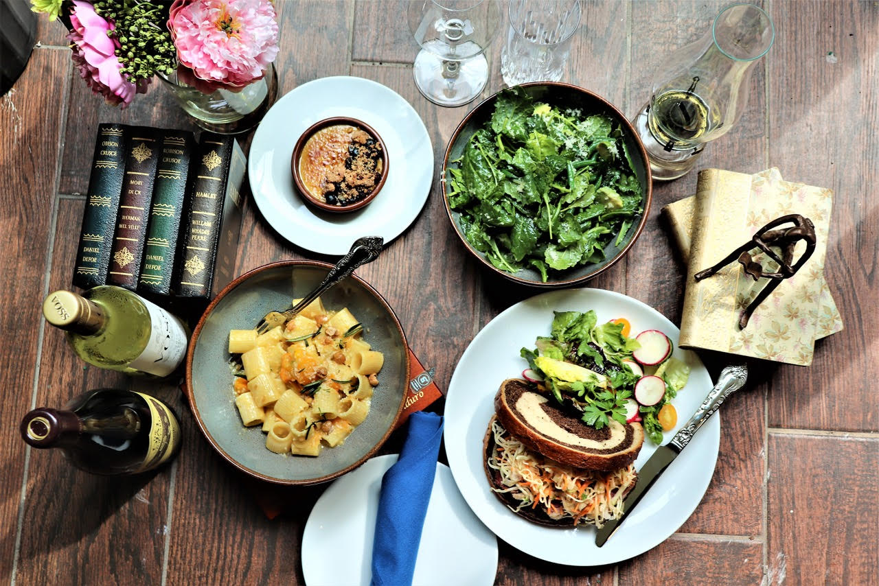 A wooden table with a food spread of salads, meat, and pastas, with wine bottles and a vase of flowers.