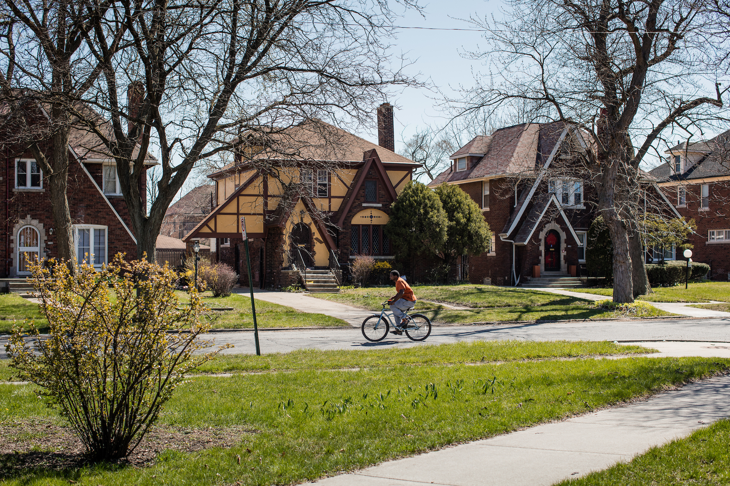 A boy rides a bike down a street lined with attractive brick homes.
