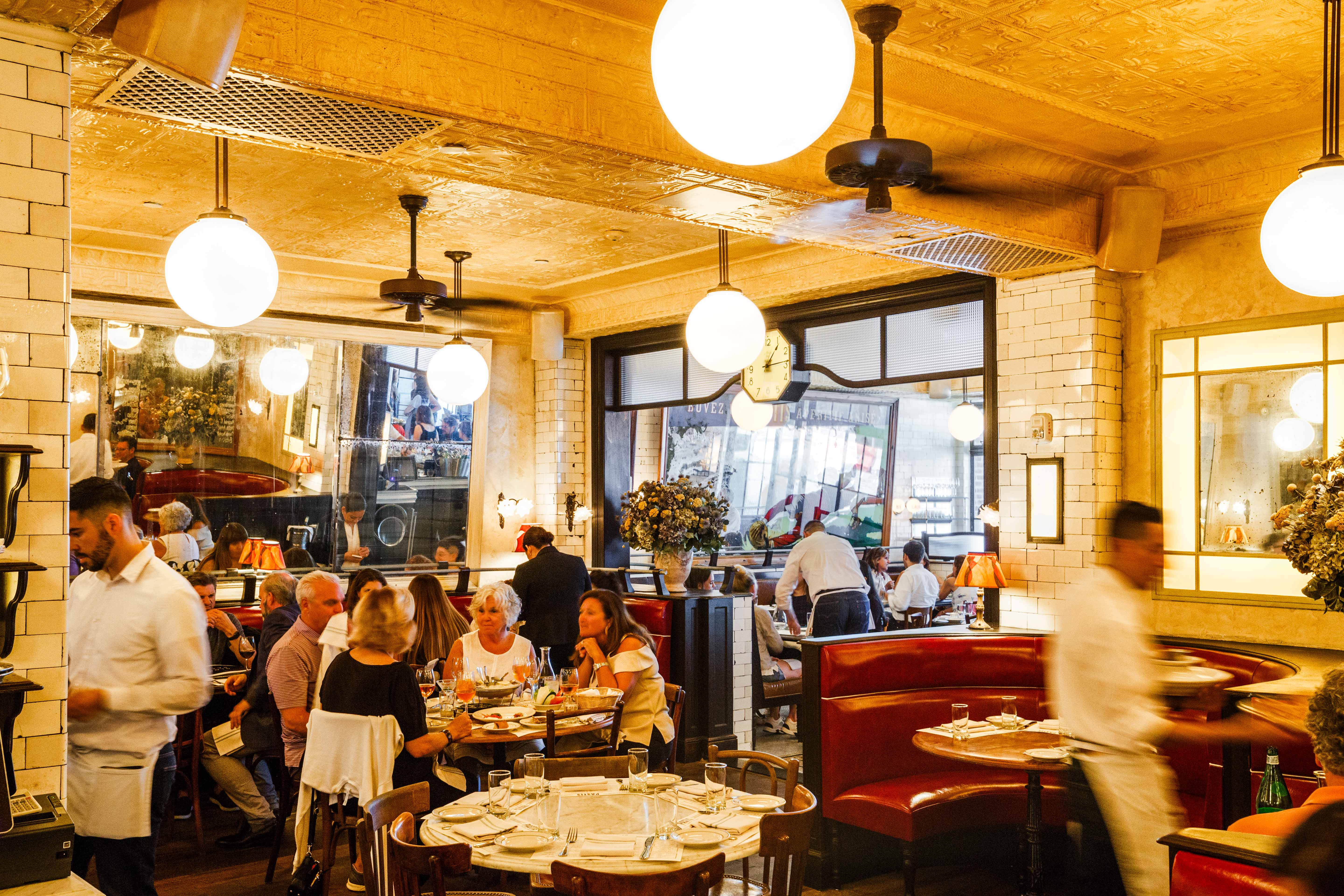 Patrons gather under gold-hued lighting for a meal at Pastis