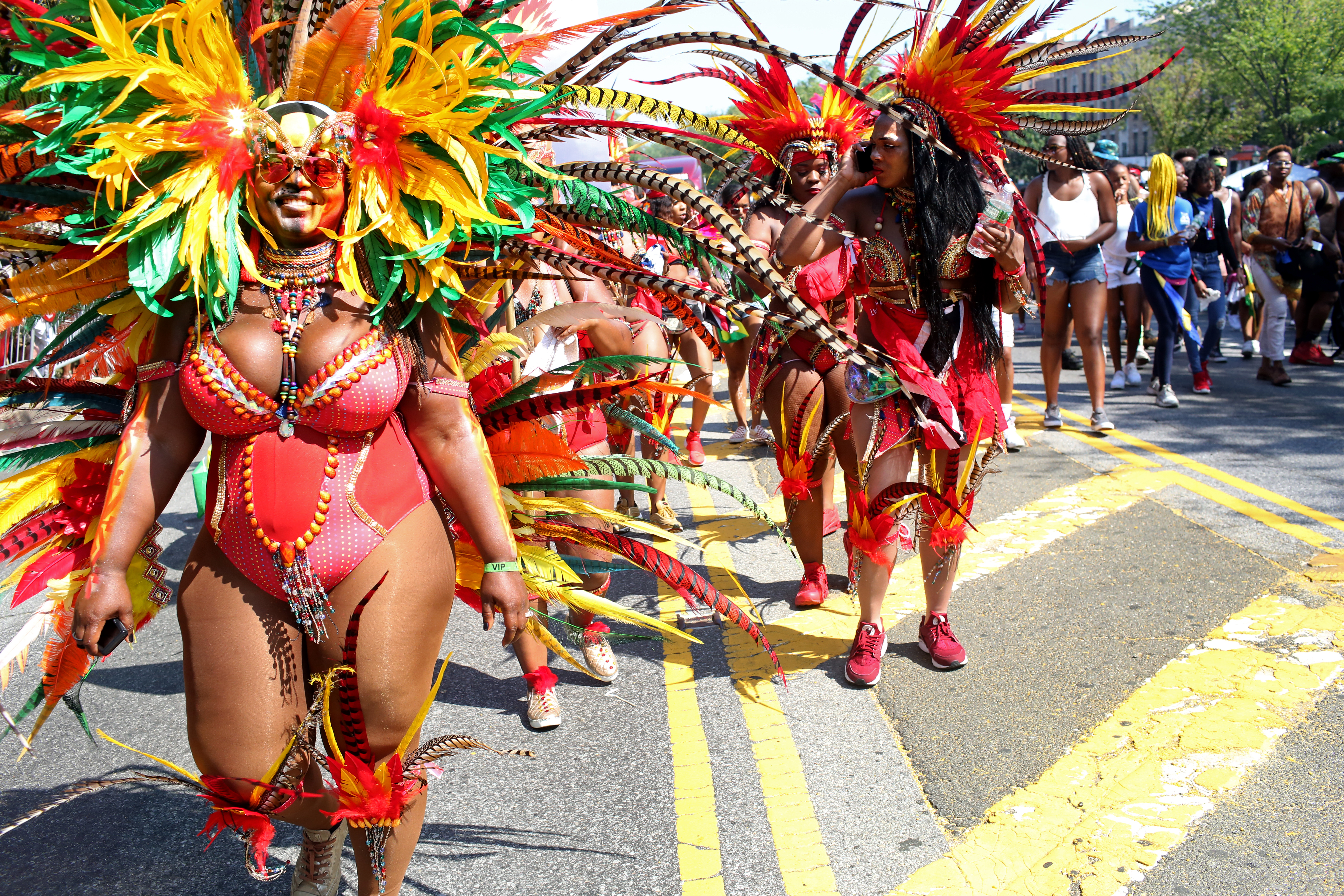Women in colorful costumes with feathered headdresses walk down a street during a large neighborhood parade.