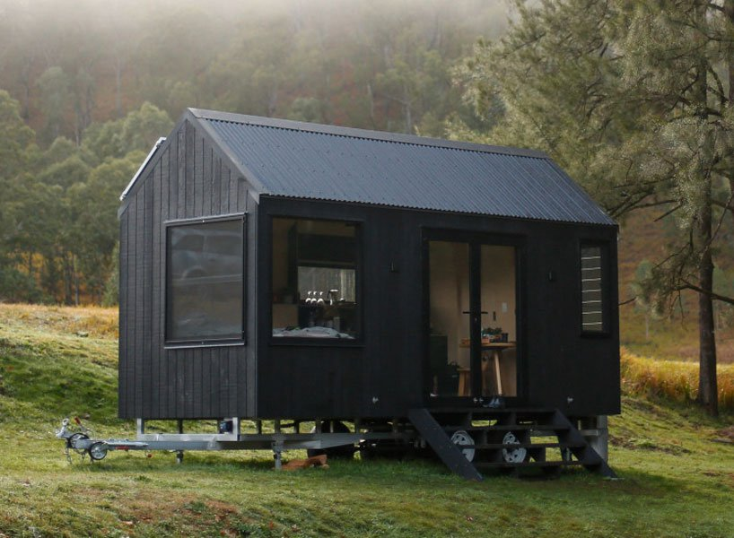 All-black tiny house on wheels featuring pitched roof and glass doors sits on grass. Trees are in the background.