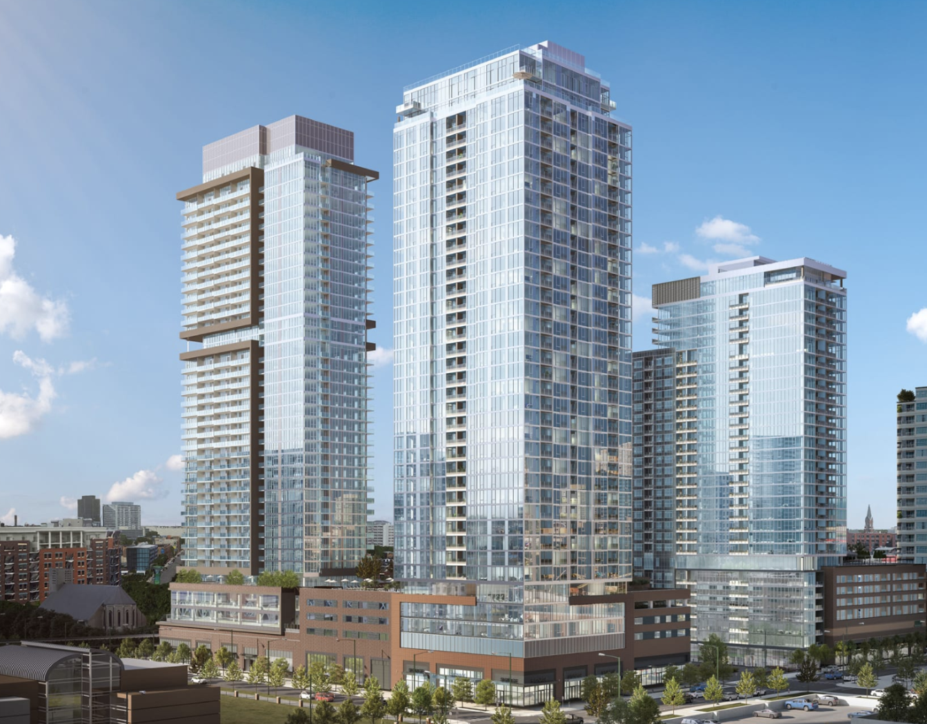 A rendering of three modern, glassy high-rise towers with masonry bases. The buildings are tightly clustered together.