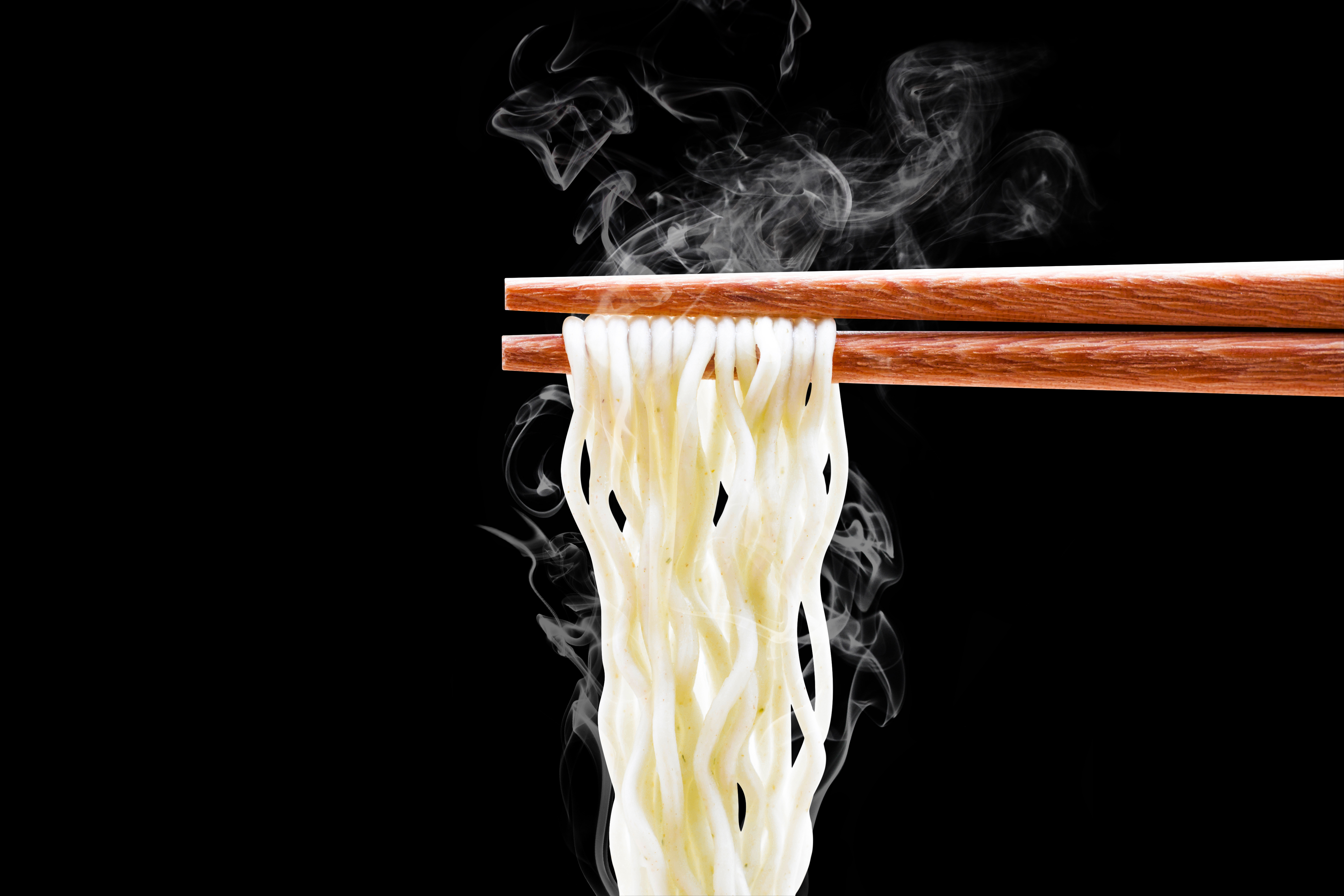 Ramen noodles held up by chopsticks against a black background