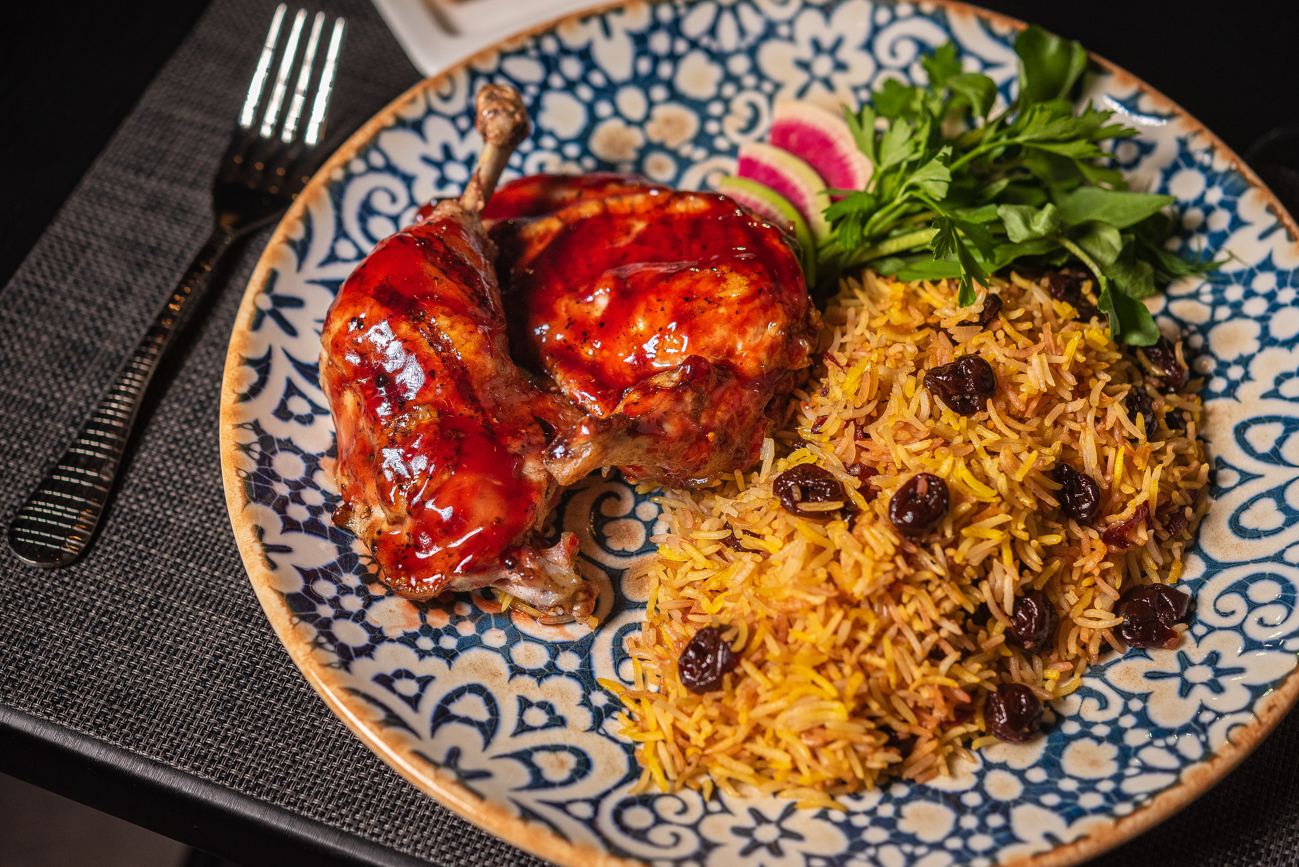 Sour cherry rice served with roasted chicken that's been glazed in a reduced pomegranate sauce