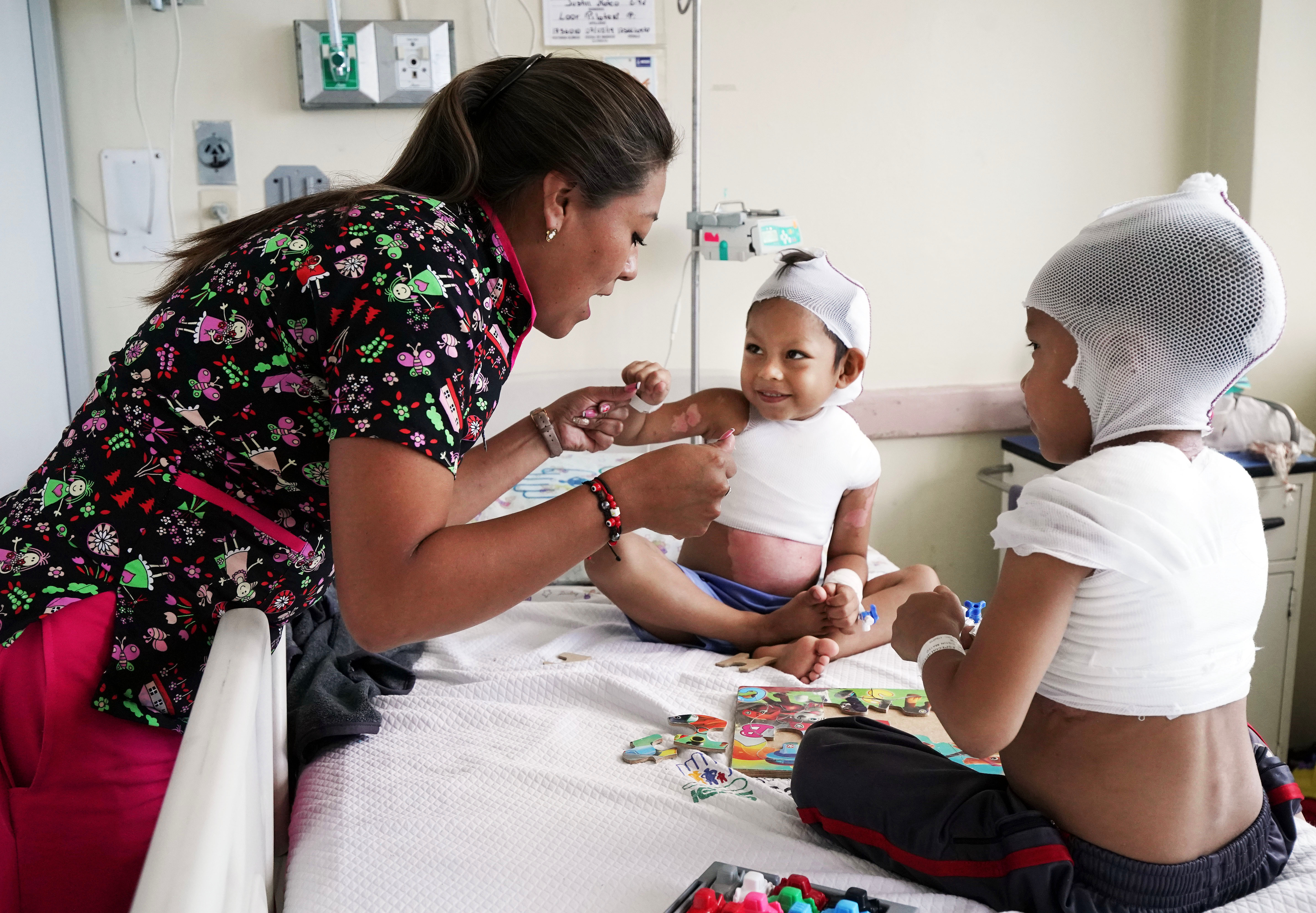 Teacher Vanessa Garcia bumps fists with burn victims Jhon Jairo Ramos Mendoza, center, and Justin Mateo Loor Pilitaxi after they finish a learning task in their hospital room at the Carlos Andrade Marin Hospital in Quito, Ecuador, on Tuesday, Aug. 27, 2019.