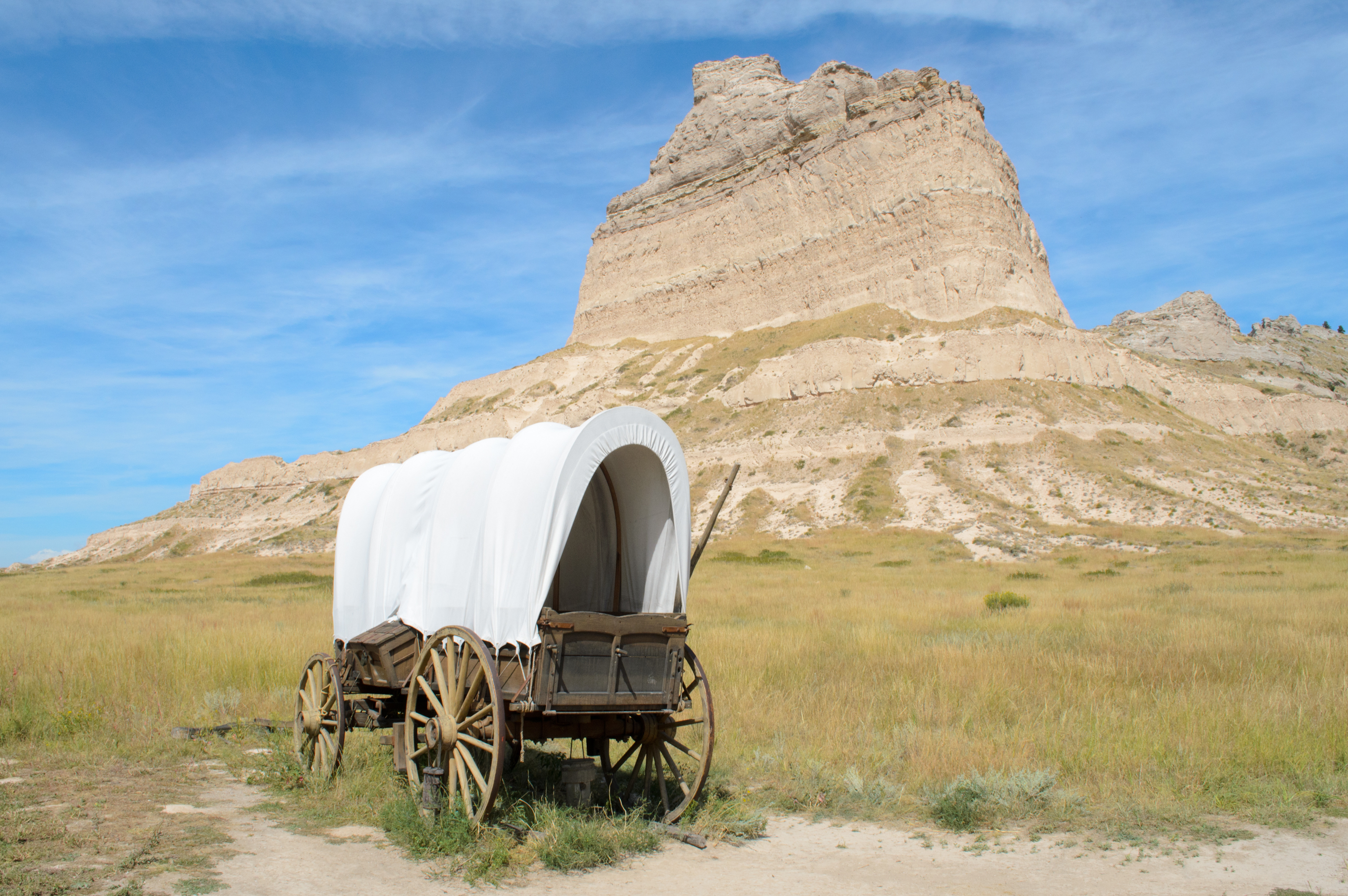 A photo of a covered wagon in open terrain on a clear day, with a large rock cropping in the background.