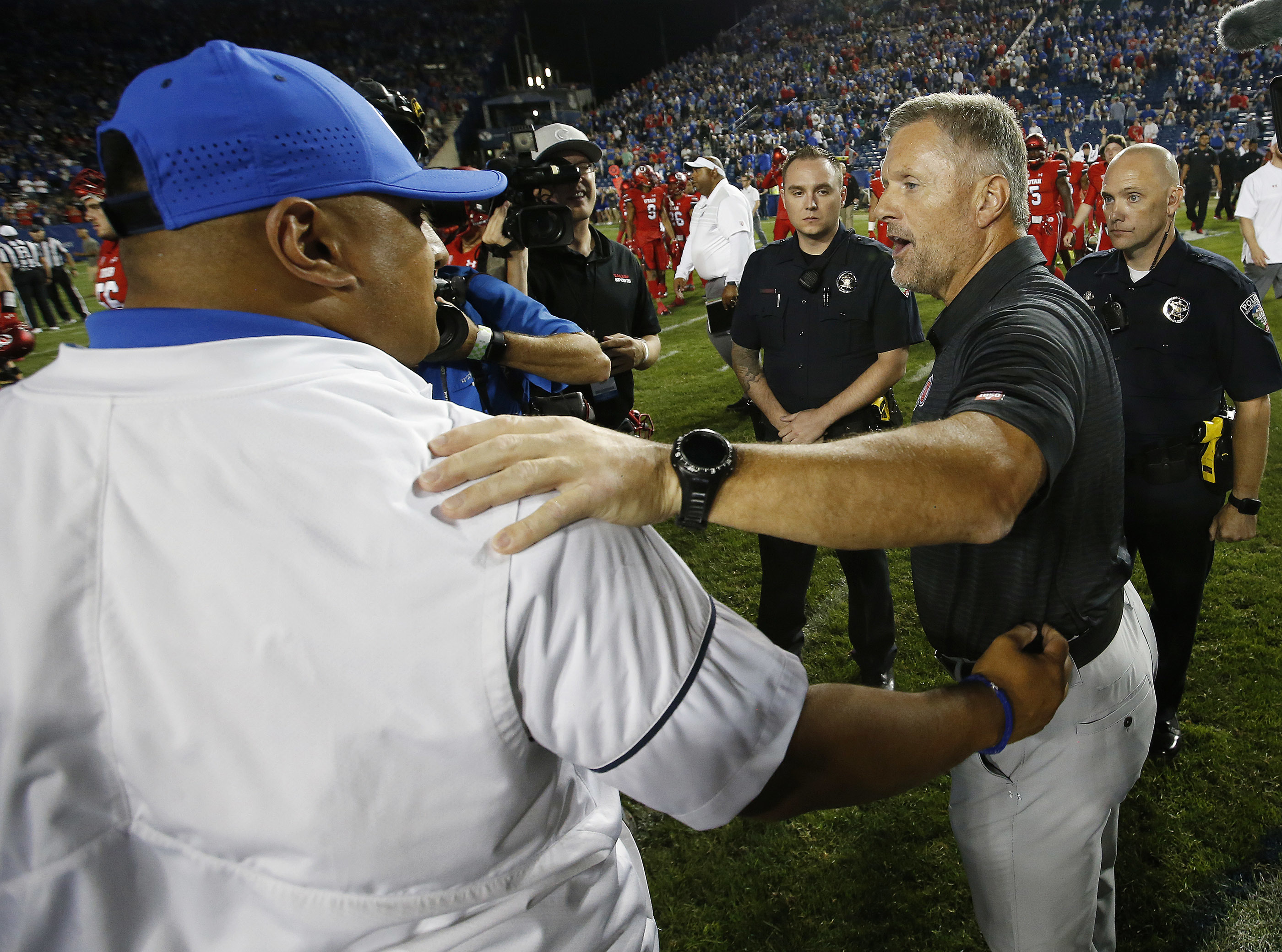 Utah coach Kyle Whittingham, right, and BYU coach Kalani Sitake greet after the game in Provo on Sunday, Sept. 10, 2017.