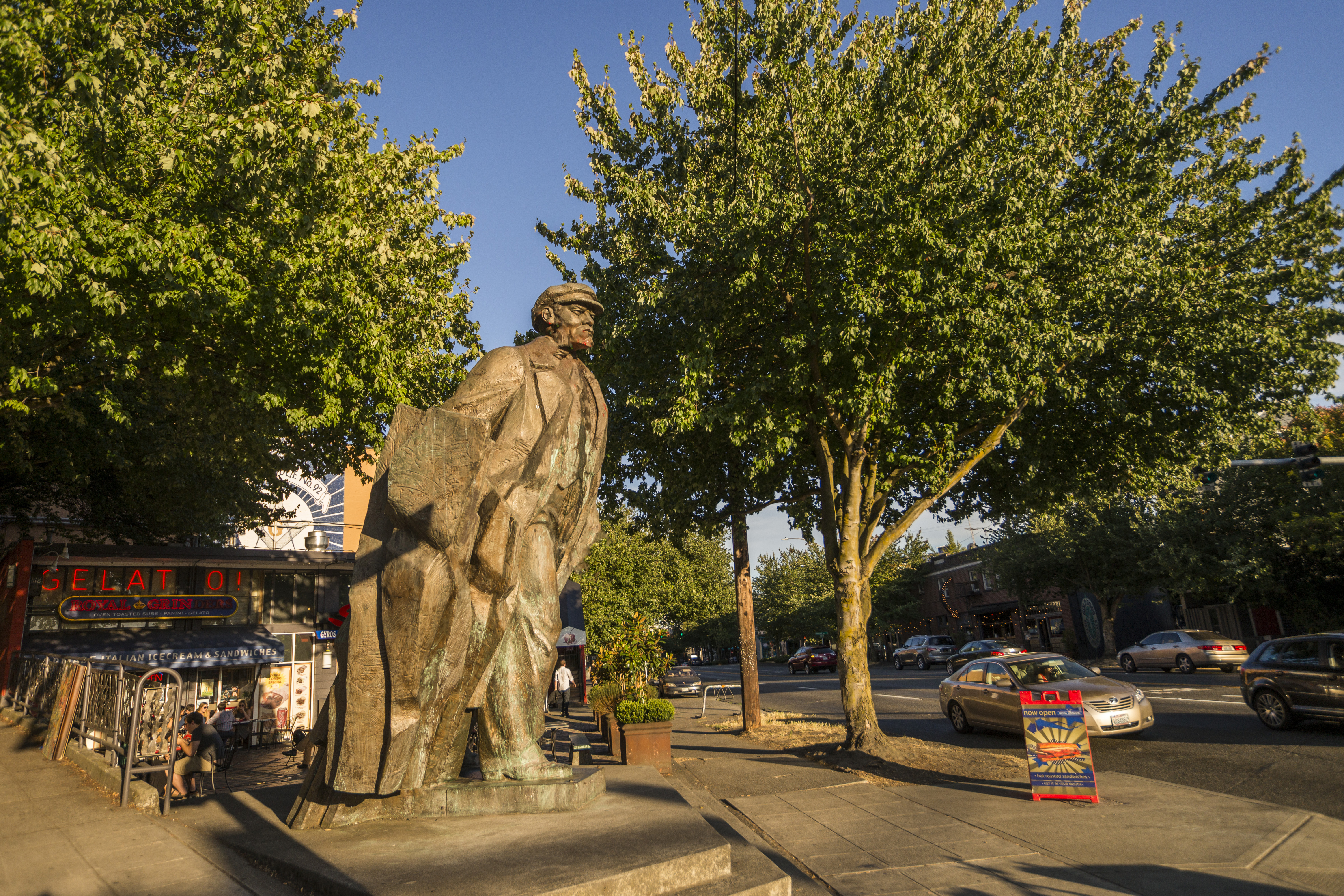 A large, bronze statue of a man, taller than the building behind it. It's overlooking a street, and it's framed by sidewalk trees on either side.