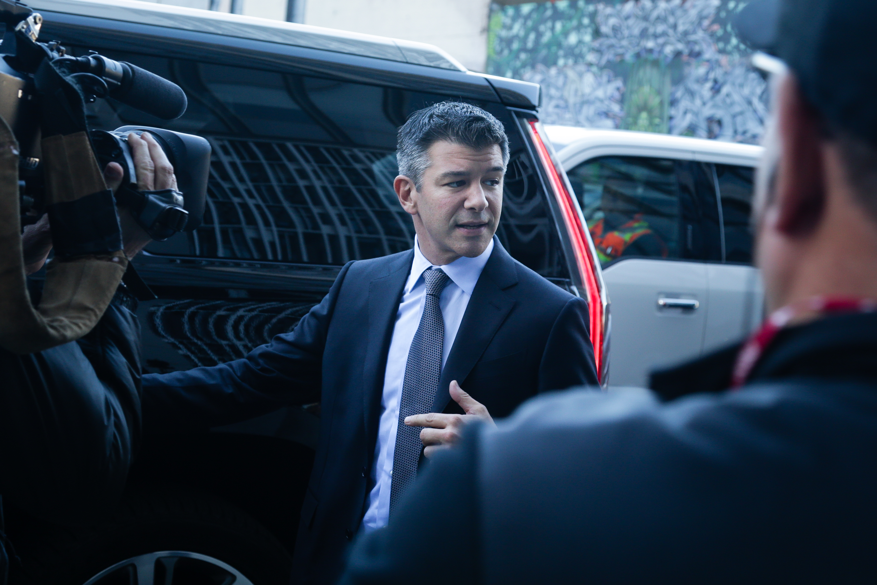 Former Uber CEO Travis Kalanick exiting a courthouse, surrounded by reporters and cameras.