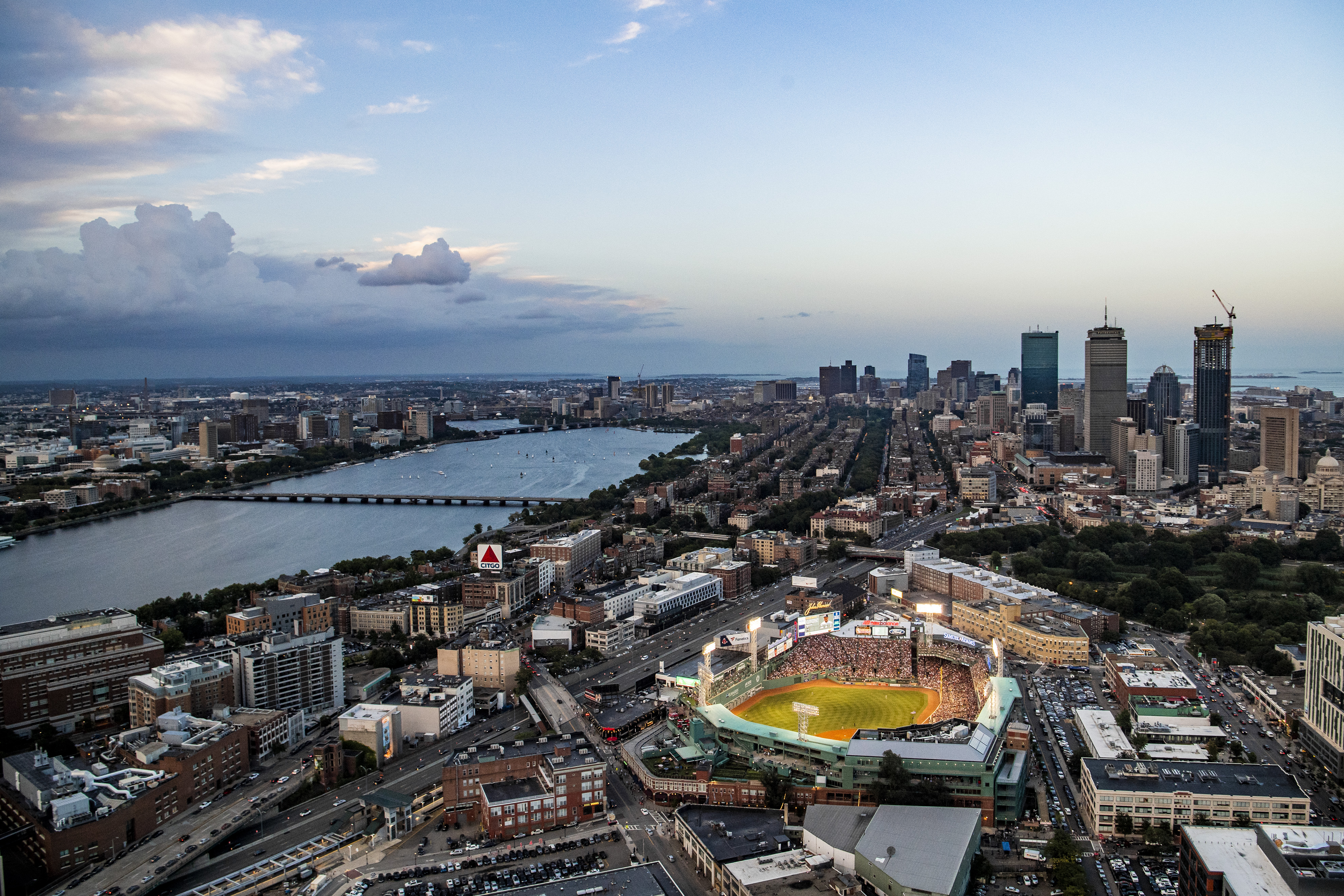 An aerial shot of a ballpark amid the City of Boston. The stadium, called Fenway Park, is illuminated, and much of the rest of the city is dark.