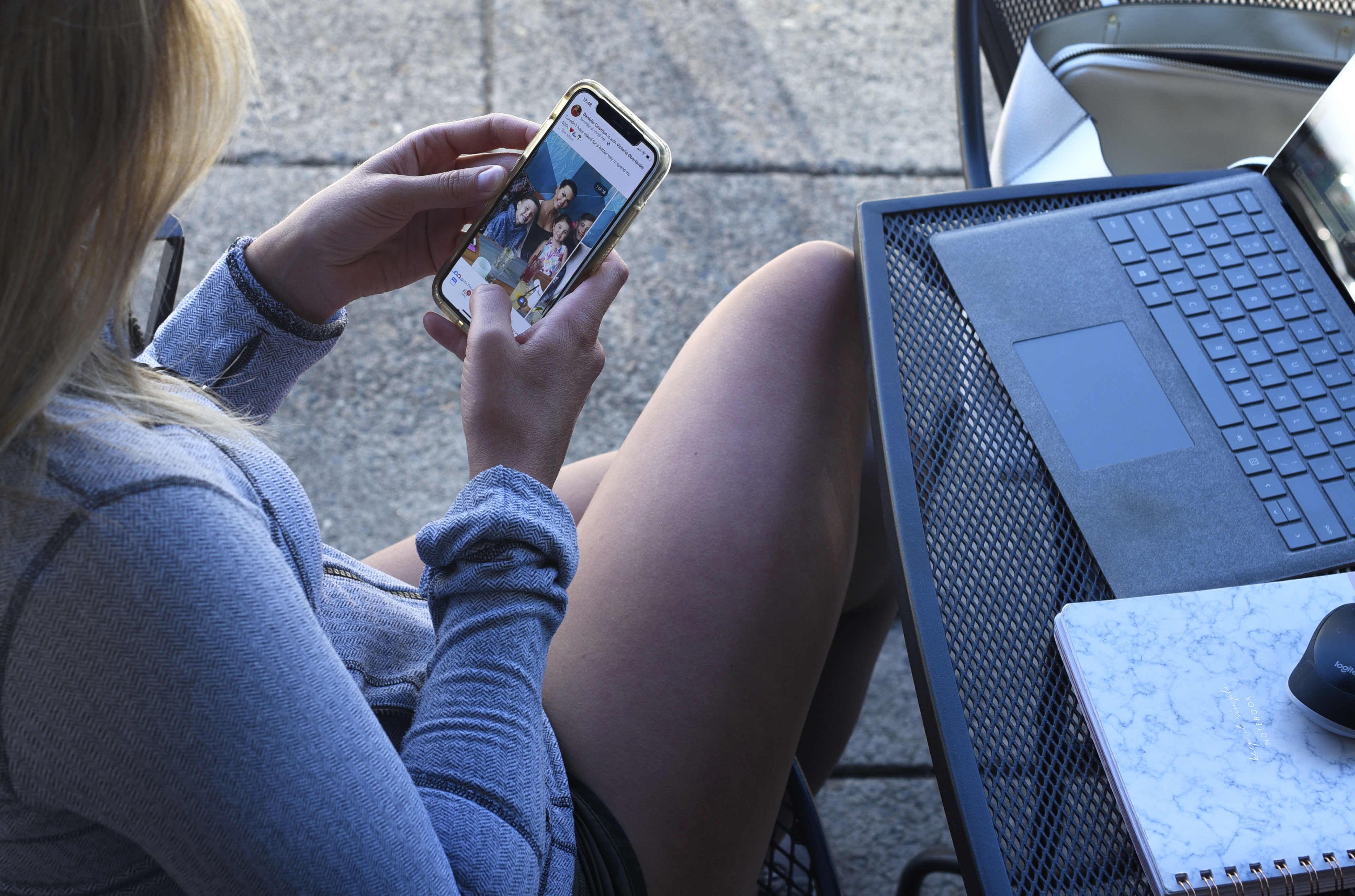 A woman sitting at an outdoor table with her laptop looks instead at her smartphone.