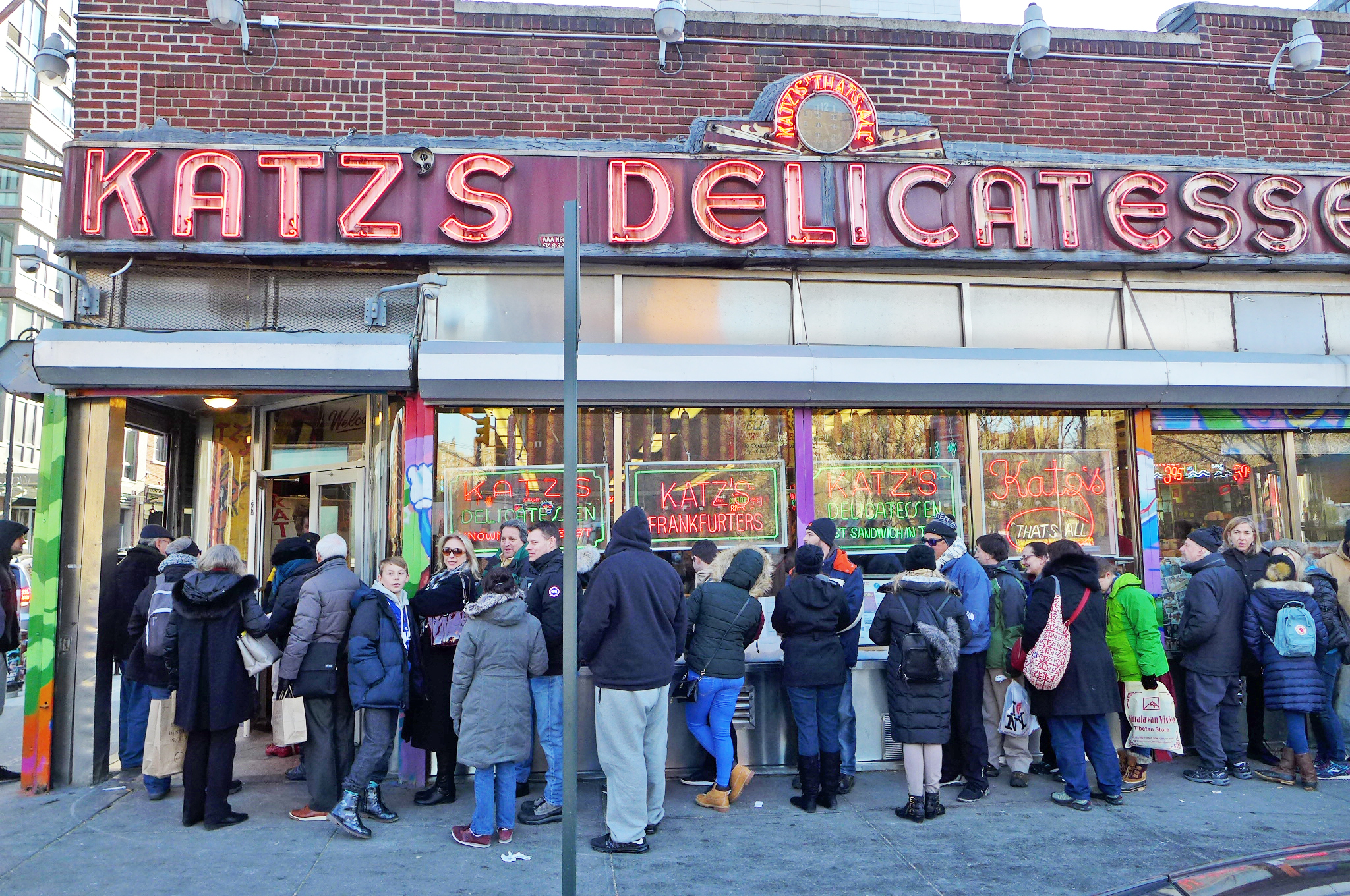 A line of people outside the deli, the front window of which is filled with neon signs