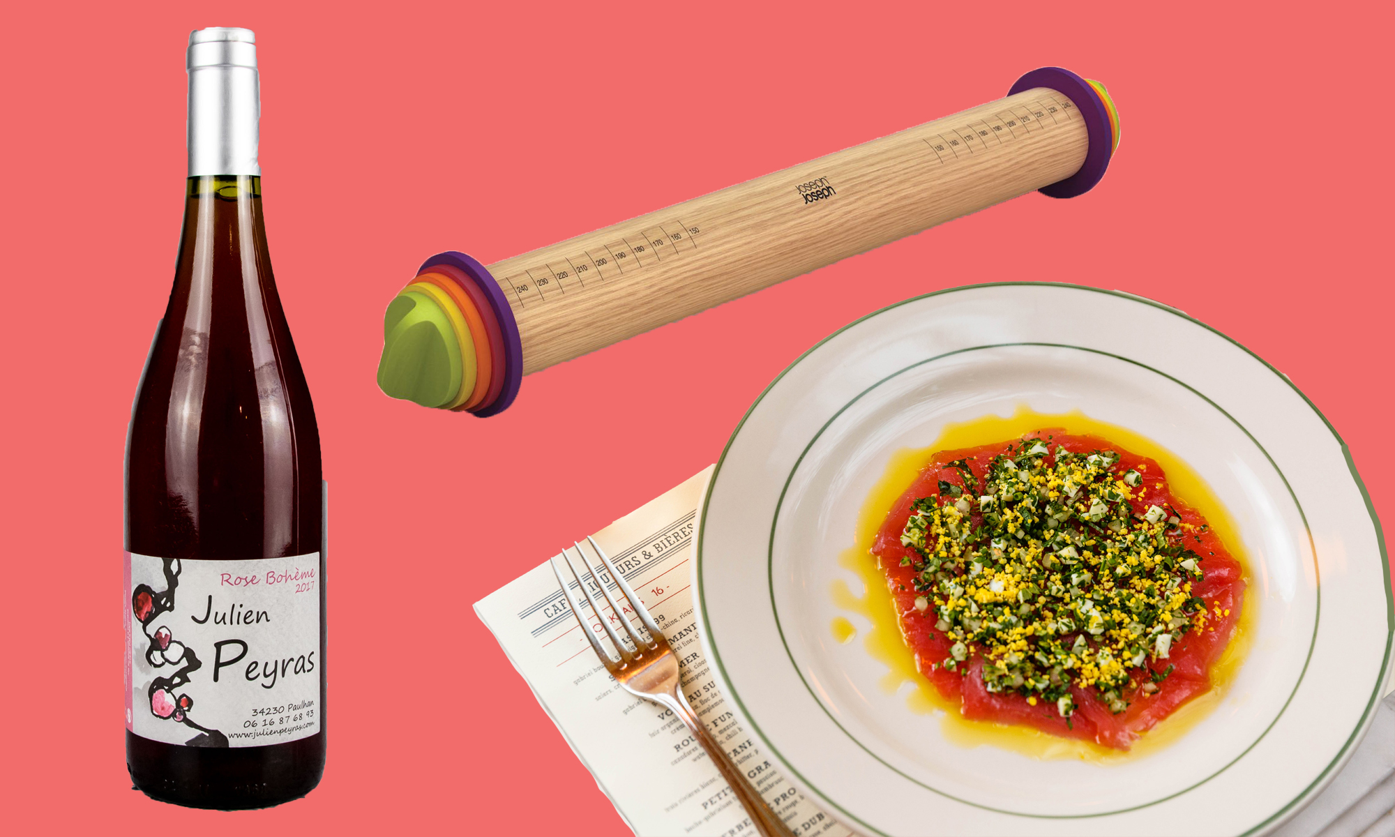 Bottle of natural rosé wine, a rolling pin, and a plate of food from Pastis, all on a vibrant coral pink background