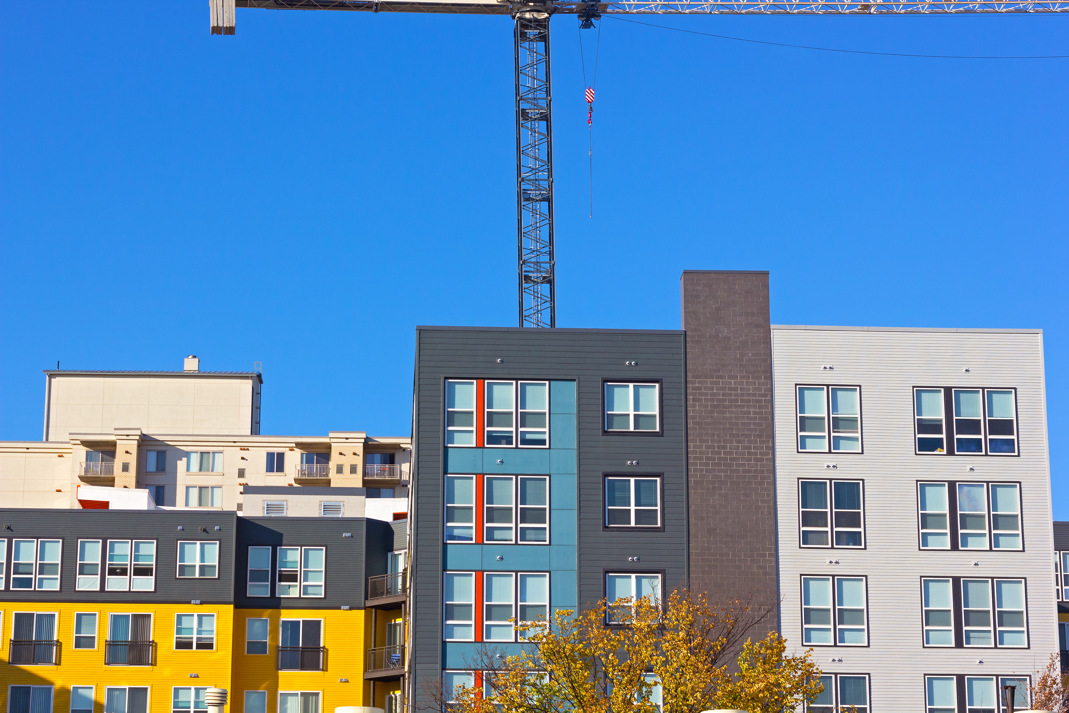 The top of modern residential buildings with a crane in the background.