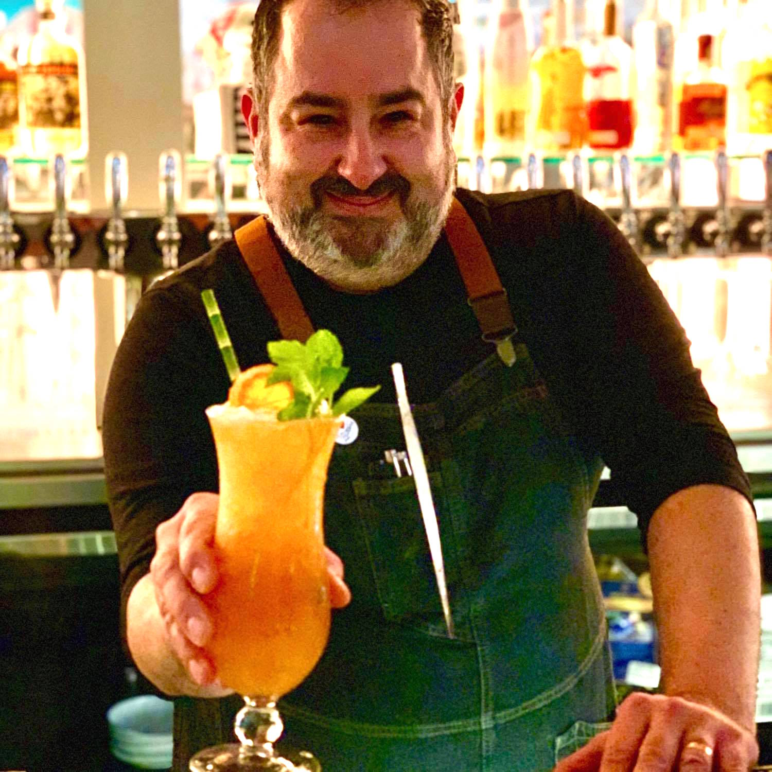 Efrain Santiago serving a cocktail with a big mint garnish behind the bar of Lolito