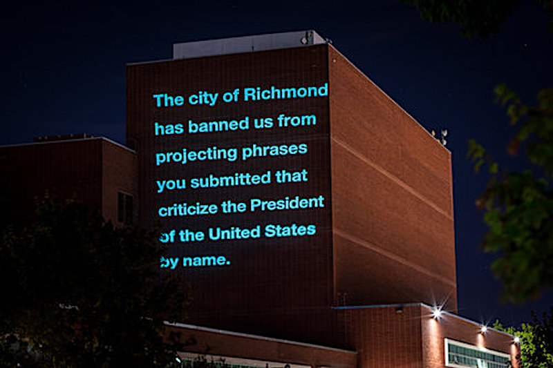 """Richmond City Hall, a six-story red-brick building, with a message projected onto the side reading in part, """"The city has banned phrases that criticize the president."""""""