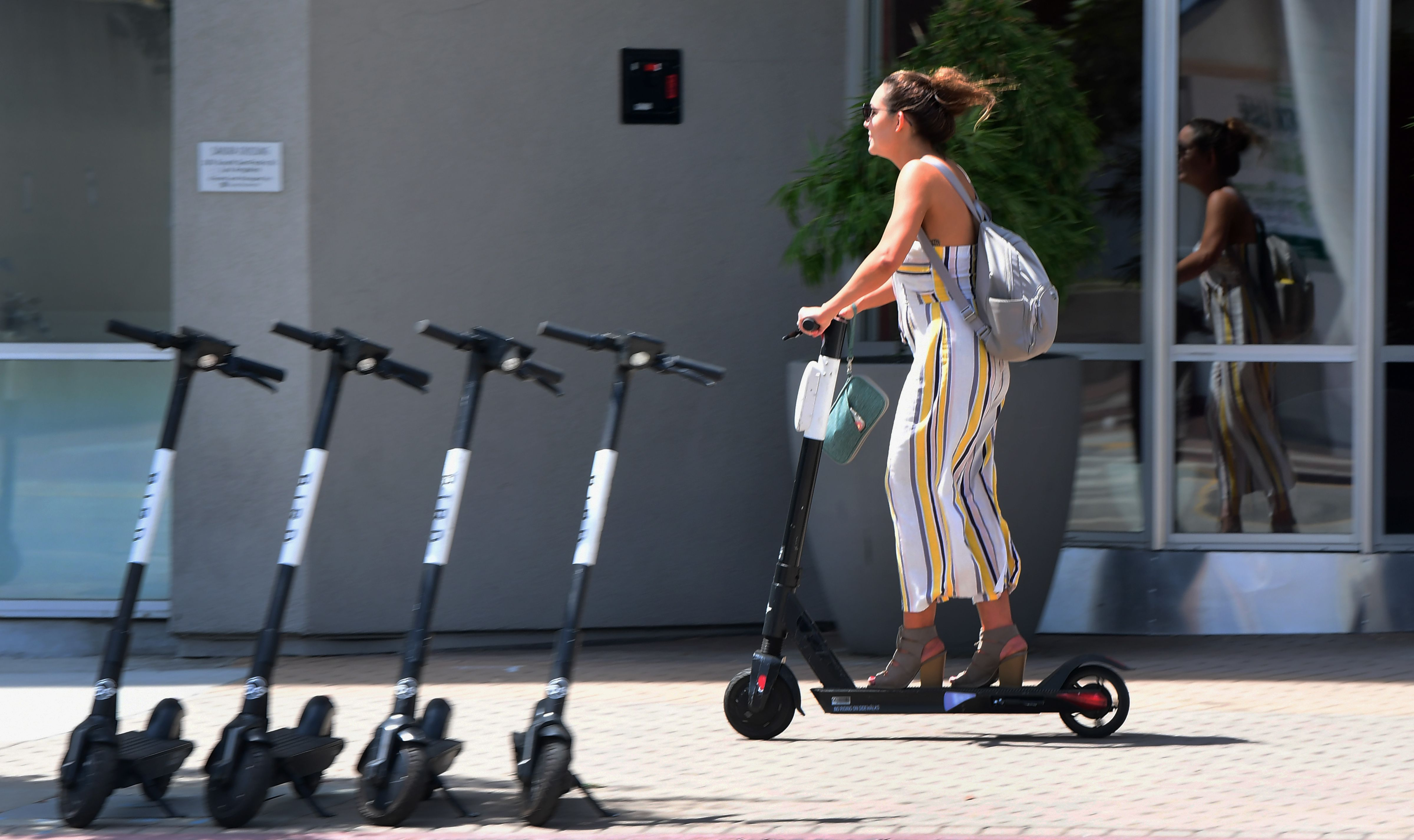 A woman in a white and yellow striped jumpsuit and  a gray backpack rides a black and white electric scooter on a sidewalk past a gray building. Four scooters are parked on the street in front of her.