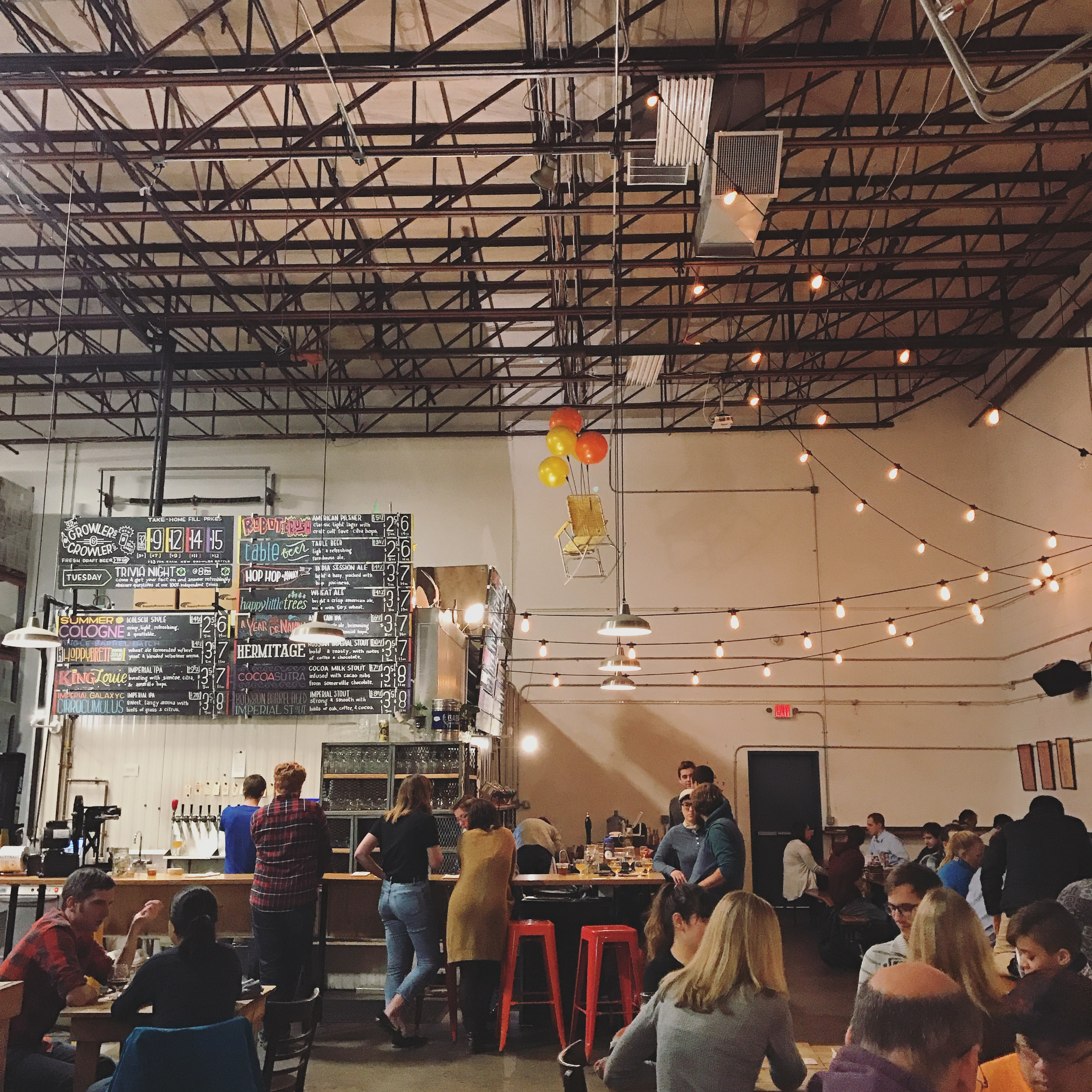 Towering ceilings accommodate a chalkboard beer list, a bar, and table seating inside a brewery