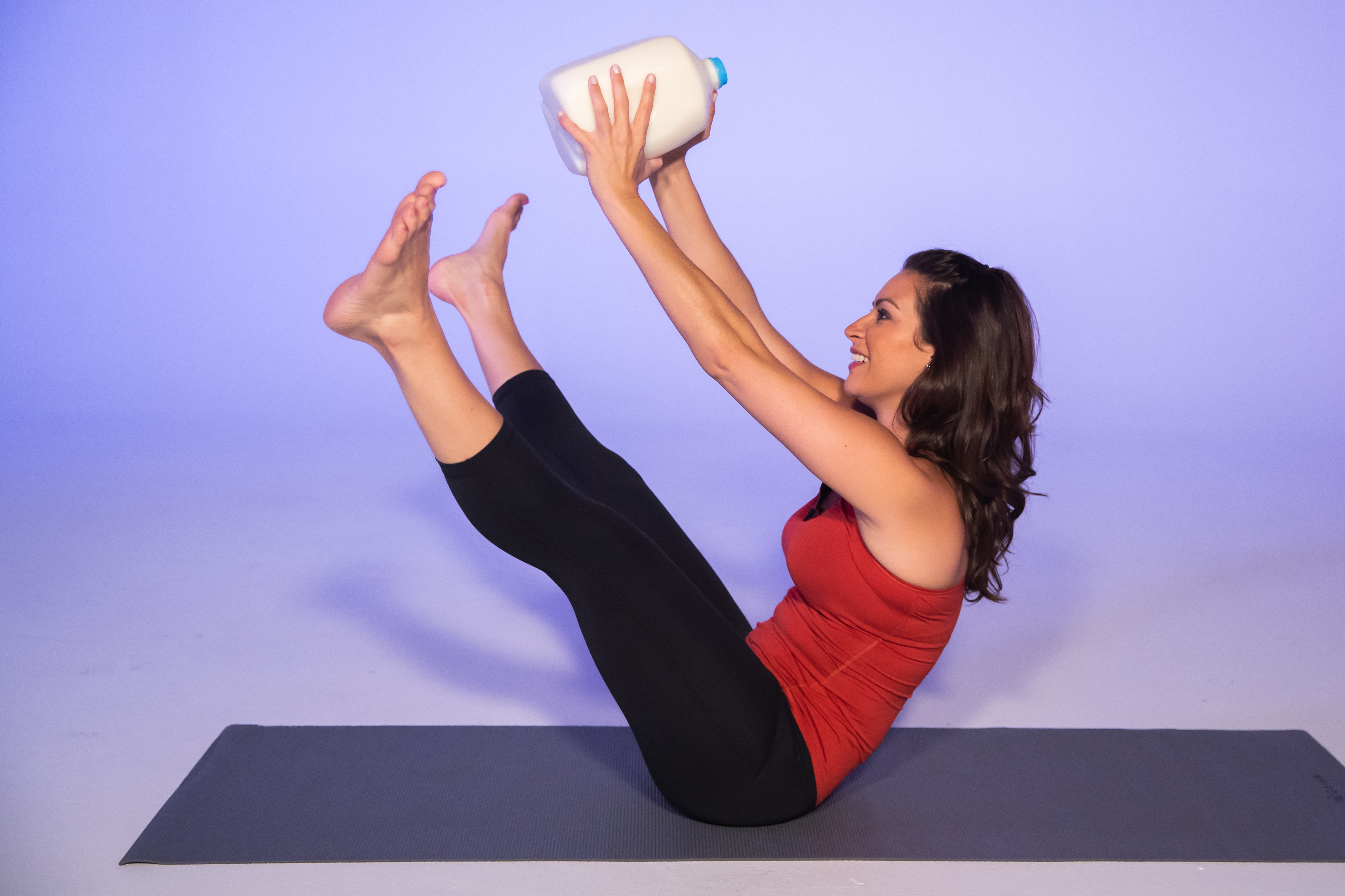 Stephanie Mansour demonstrates how to use a gallon of milk as a weight in this V-sit and reach workout to strengthen and tone core muscles.