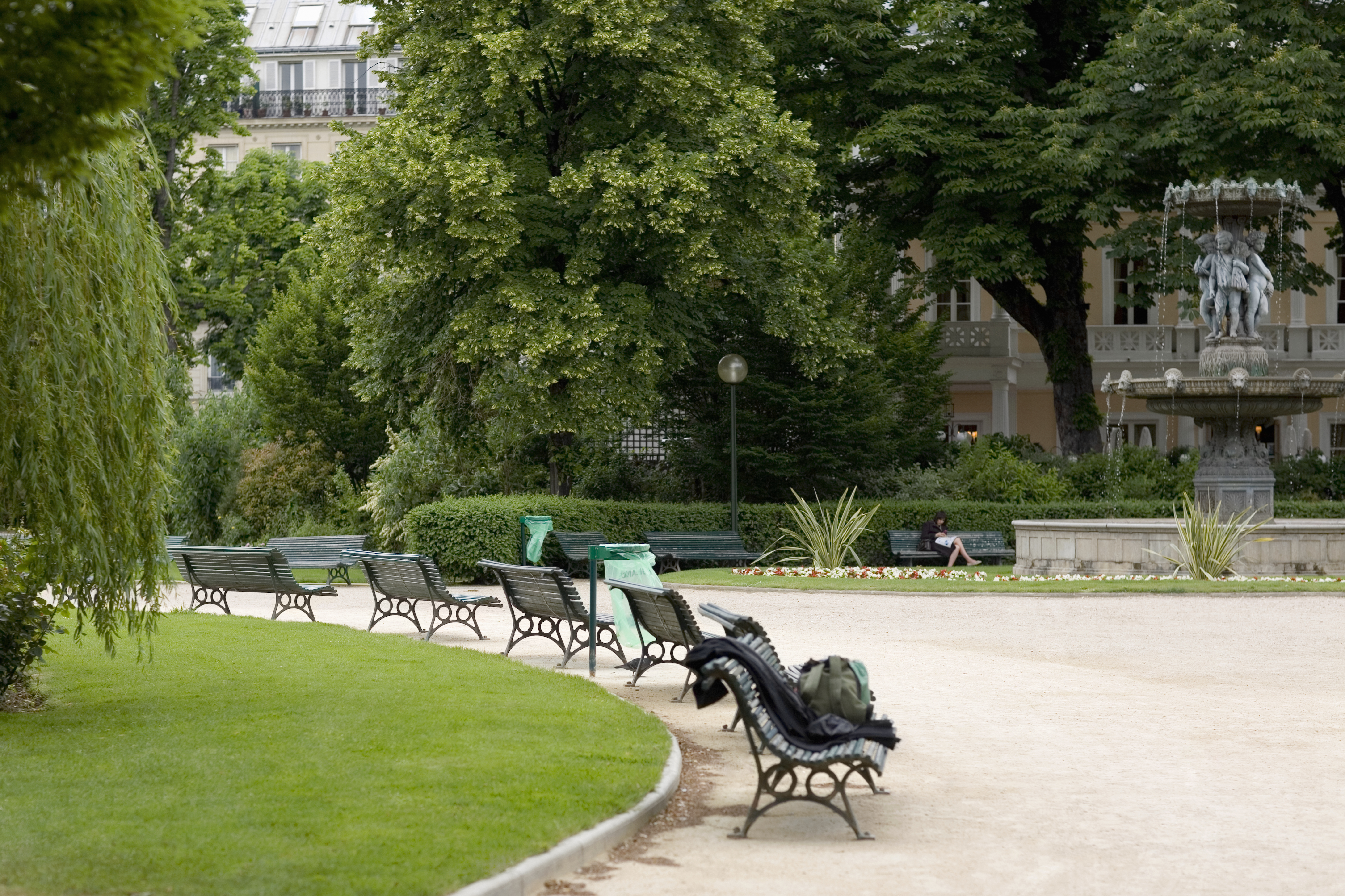 A path in a Parisian park is lined with a series of old green benches, surrounded by lawns and trees. There is a fountain to the right side.