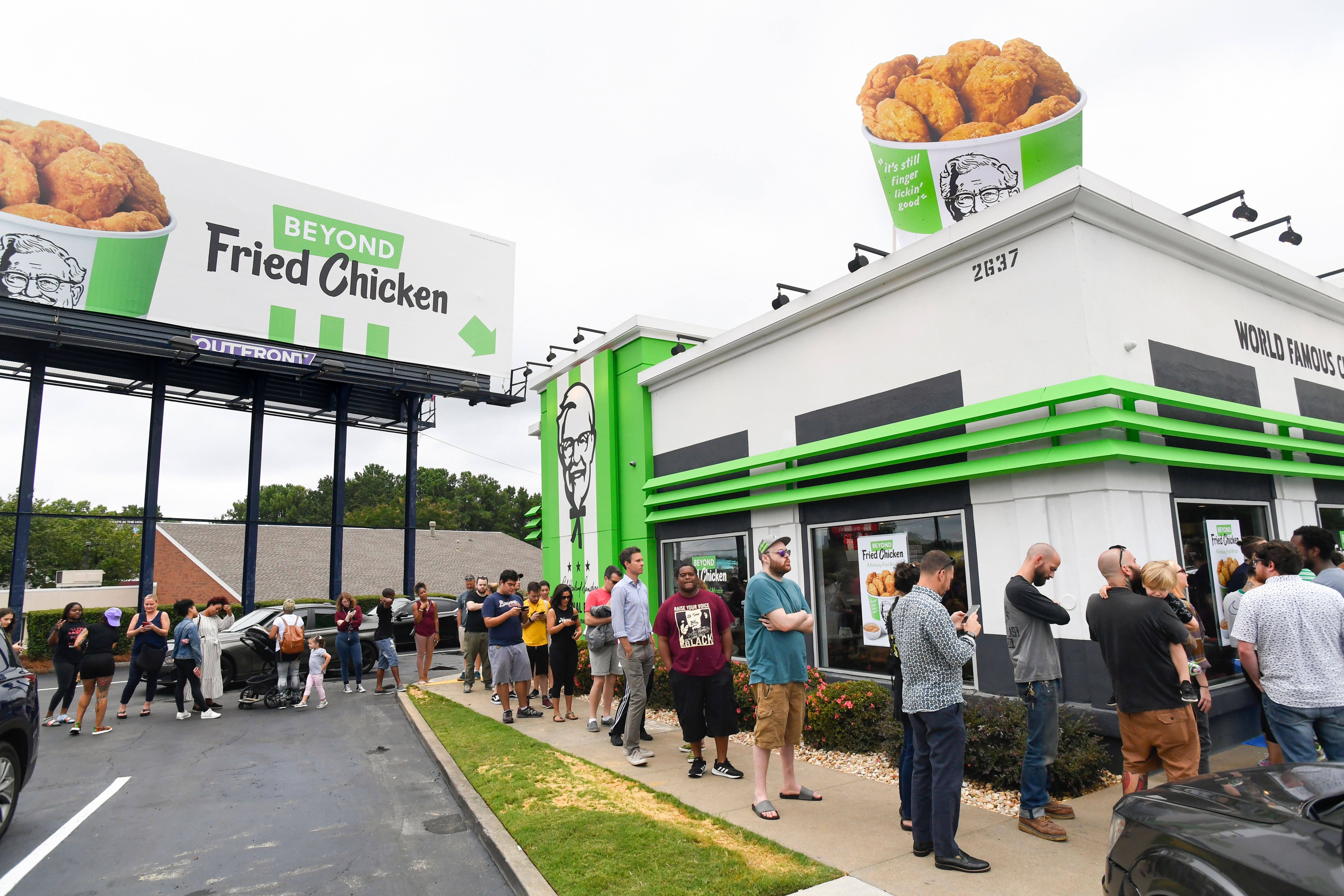"""A KFC store decorated with green coloring and """"Beyond Fried Chicken"""" promotional materials, with a long line of customers waiting outside the store."""